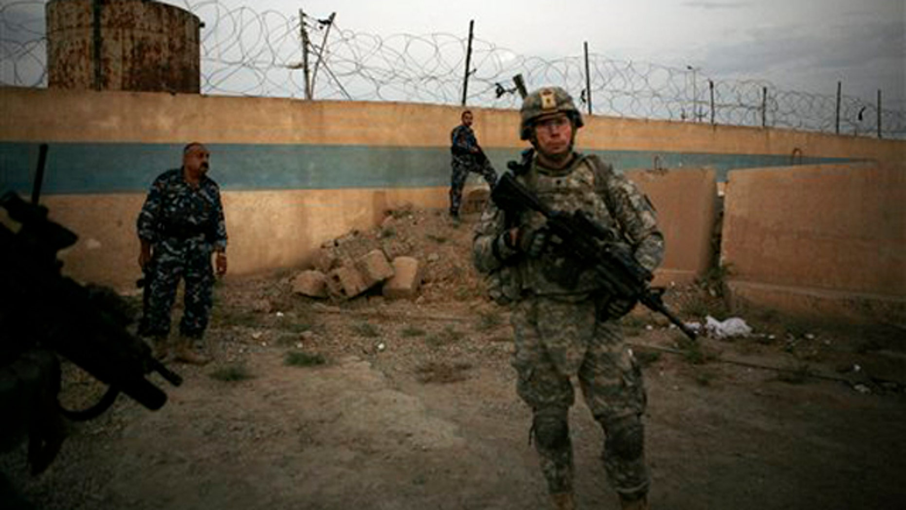 A U.S. Army soldier from 1st Battalion, 14th Infantry Regiment stands with Iraqi policemen outside an Iraqi police station Sept. 1 in Hawija, north of Baghdad, Iraq. (AP Photo)