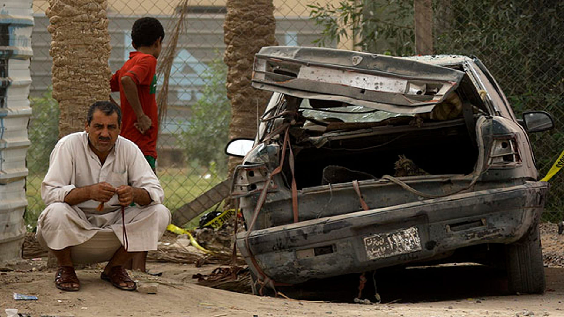 Oct. 1: A man sits next to his damaged car at the scene of a car bomb attack in a town just outside Hillah, about 60 miles south of Baghdad, Iraq.