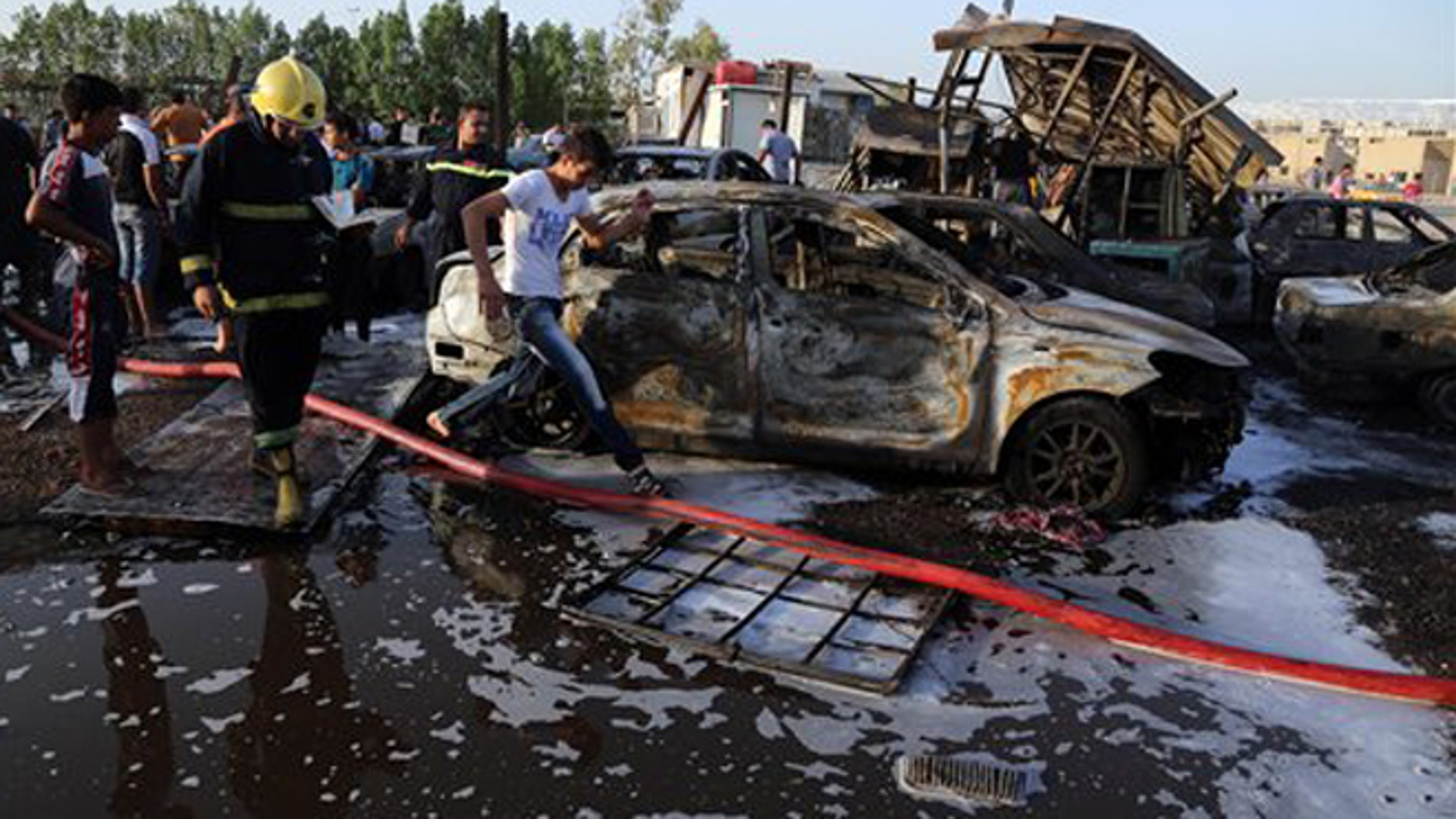 Aug 15, 2015: Civilians and security forces gather at the scene of a deadly car bomb in the Habibiya neighborhood of Sadr City, Baghdad, Iraq.