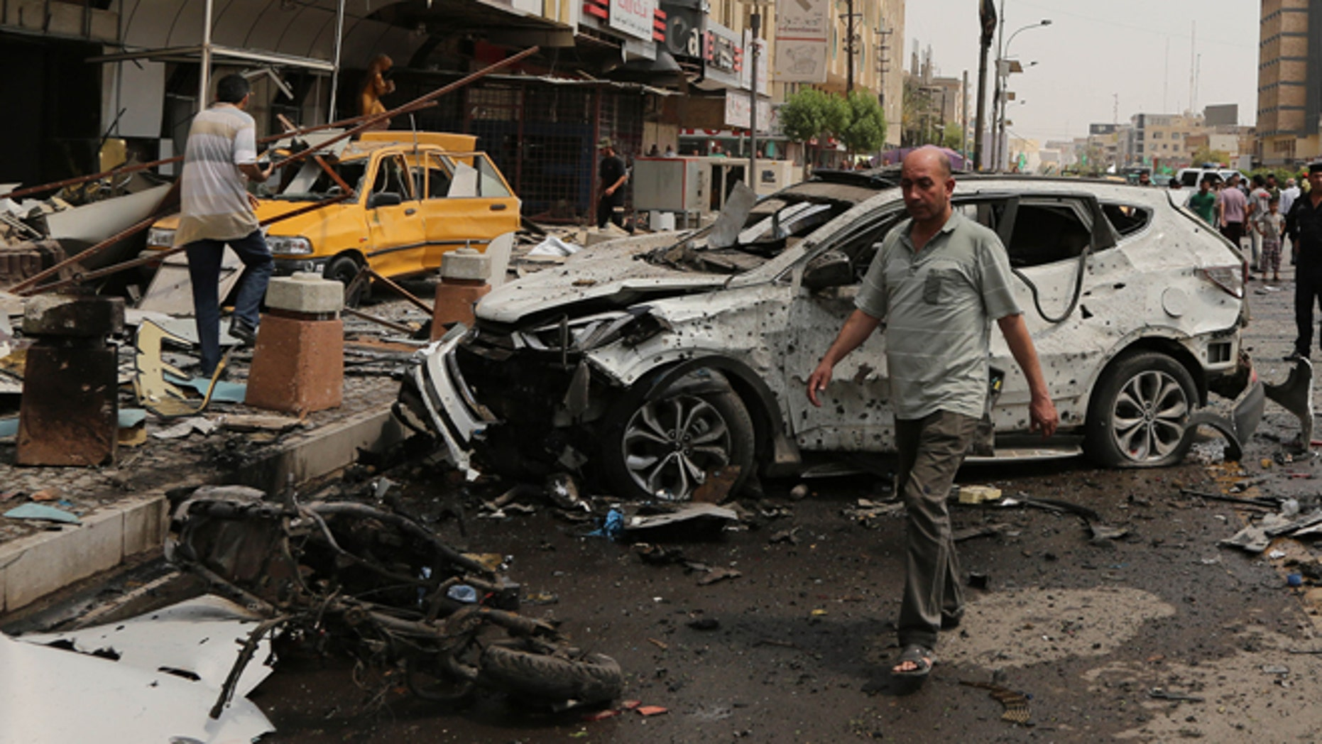 May 9, 2015: Civilians and security forces inspect the scene of a car bomb explosion in Karrada neighborhood, Baghdad, Iraq. (AP)