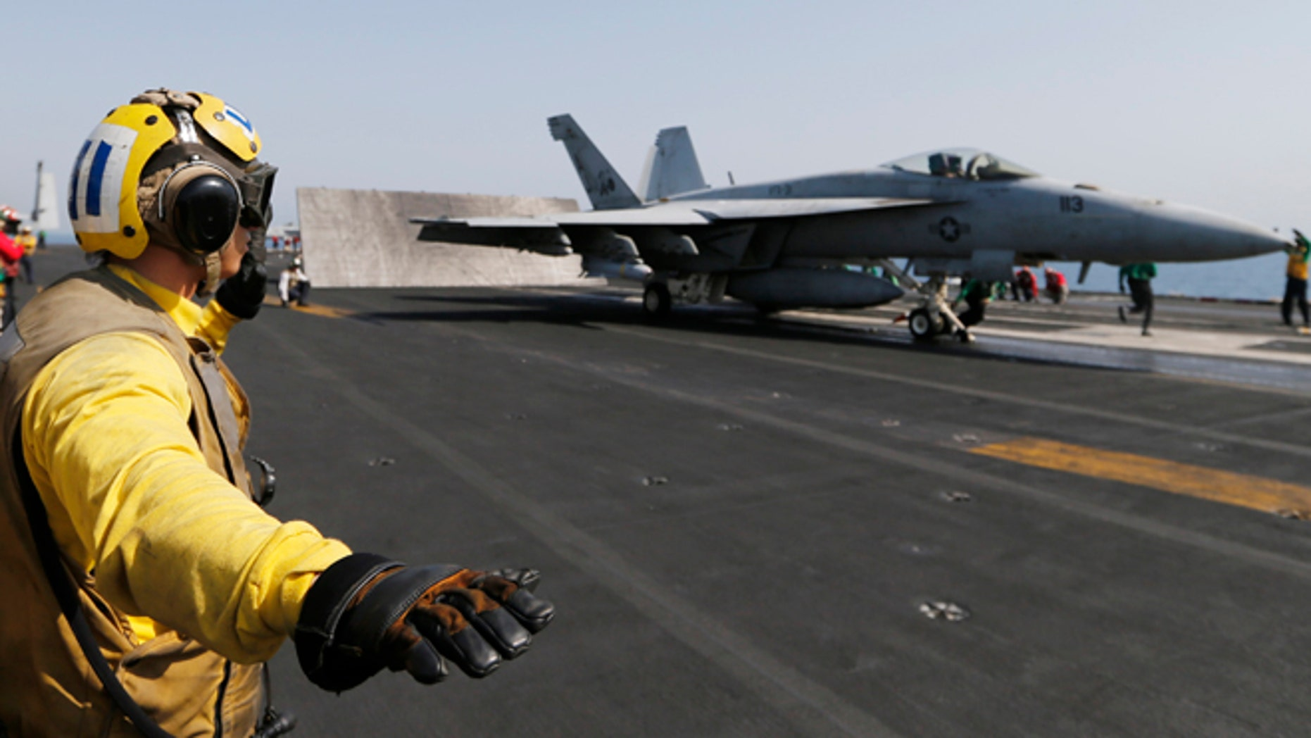Aug 12, 2104: Flight deck crew member confirms the deck is all clear before a F/A-18C Hornet of Strike Fighter Squadron (VFA-87) take offs the aircraft carrier USS George H.W. Bush (CVN 77), in the Gulf.