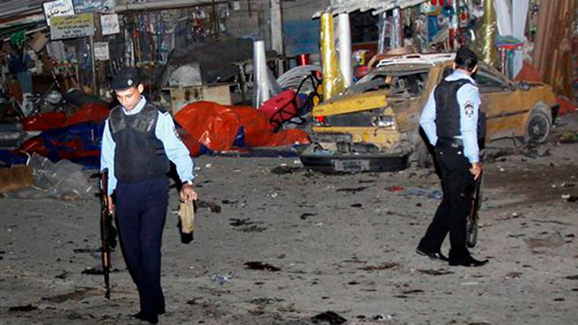 Police inspect the scene of a bomb attack in Basra, 340 miles southeast of Baghdad, Iraq, Thursday, Nov. 24, 2011.