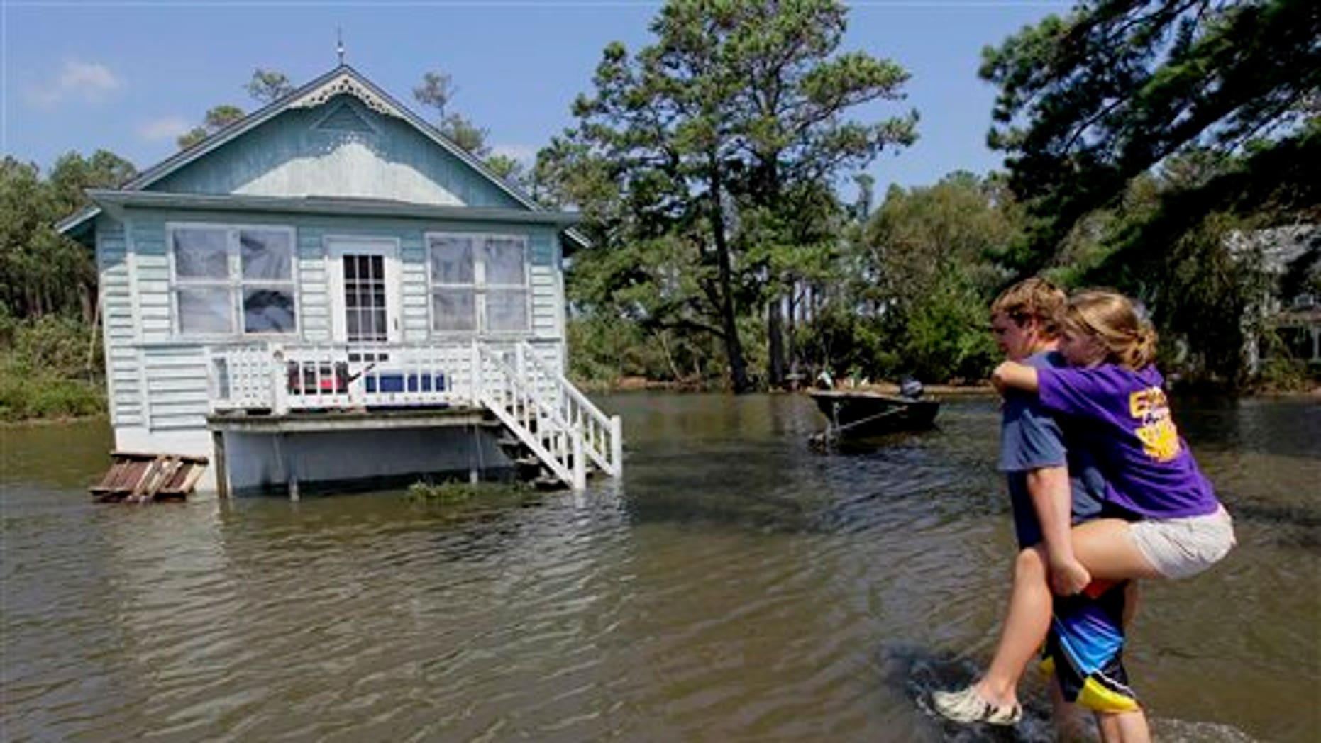 Aug. 28: Residents of Stumpy Point, N.C. make their way into their flooded home following the effects of Hurricane Irene.  Flood waters rose all across New Jersey on Sunday, closing roads from side streets to major highways as Hurricane Irene weakened and moved on, leaving 600,000 homes and businesses without power.
