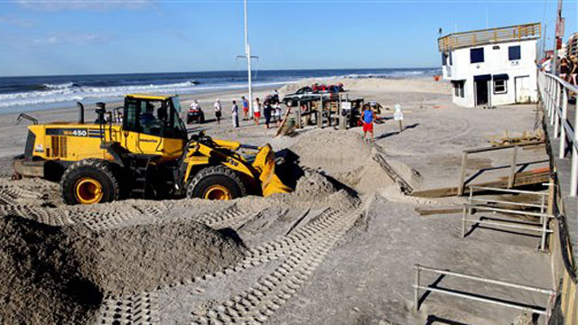 Cleanup continues near a dislodged lifeguard shack, now against the boardwalk in Long Beach, N.Y. Monday, Aug. 29, 2011, after it was knocked off its footing on the beach during Tropical Storm Irene Sunday in Long Beach, N.Y. (AP Photo/Craig Ruttle)