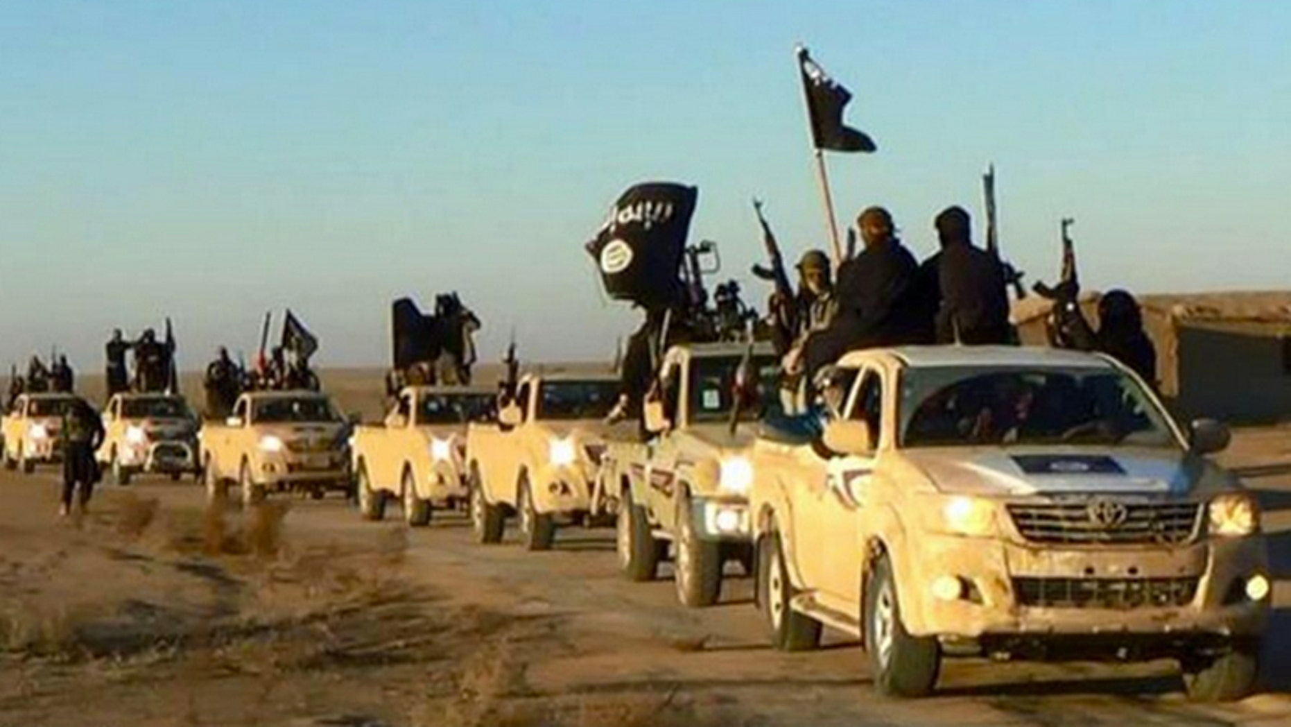In this undated file photo released online in the summer of 2014 on a militant social media account, which has been verified and is consistent with other AP reporting, militants of the Islamic State group hold up their weapons and wave its flags on their vehicles in a convoy on a road leading to Iraq, in Raqqa, Syria.
