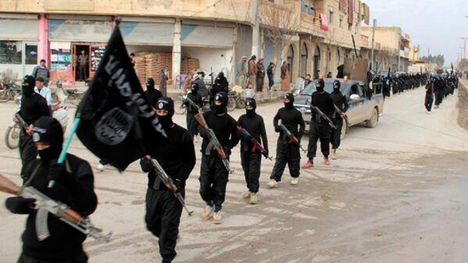 Islamic State group fighters marching. A California man has pleaded guilty to aiding the terrorist organization.