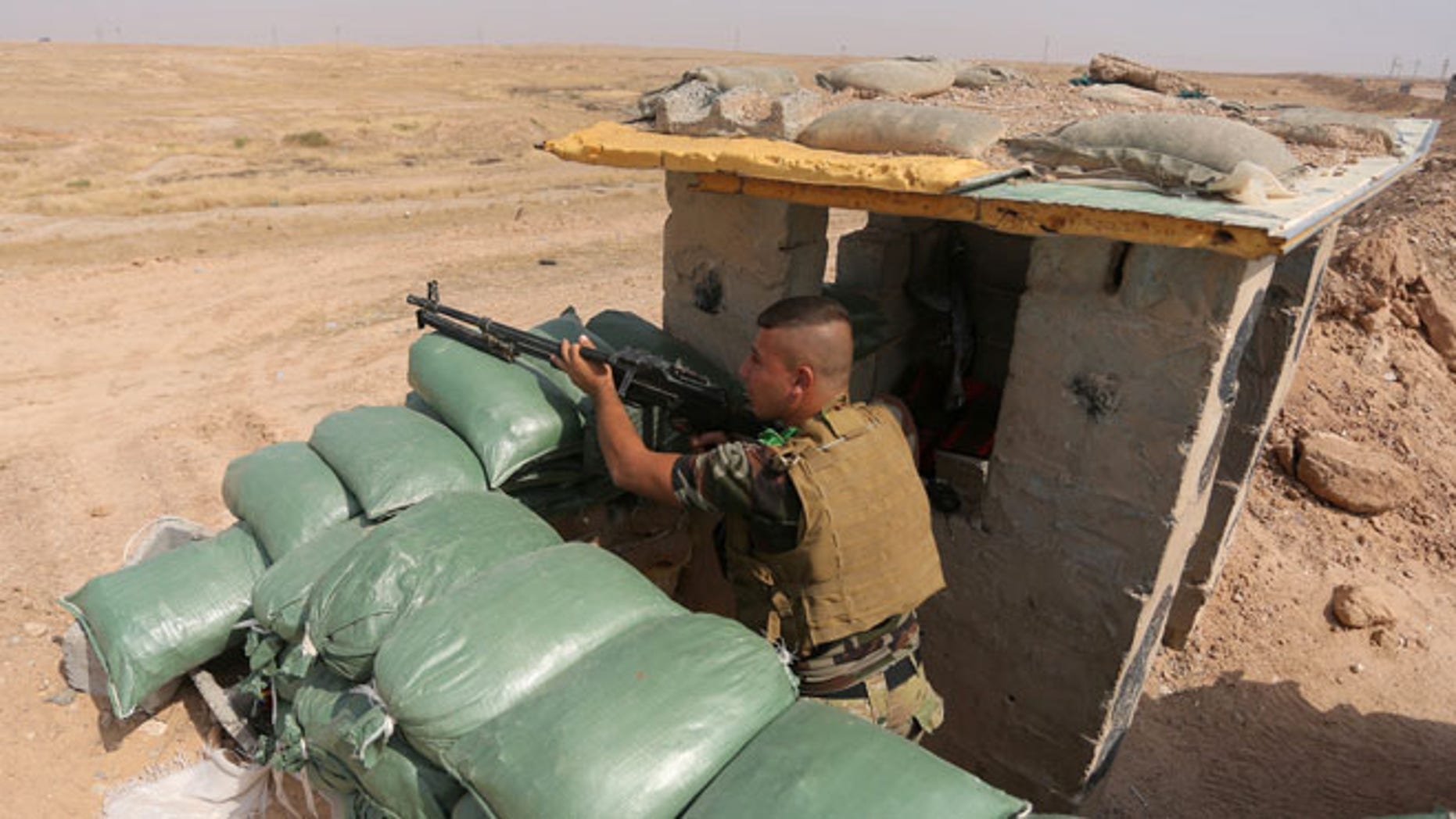 Oct. 2, 2014: An Iraqi Shiite militiamen takes cover after clashes with militants from the Islamic State group