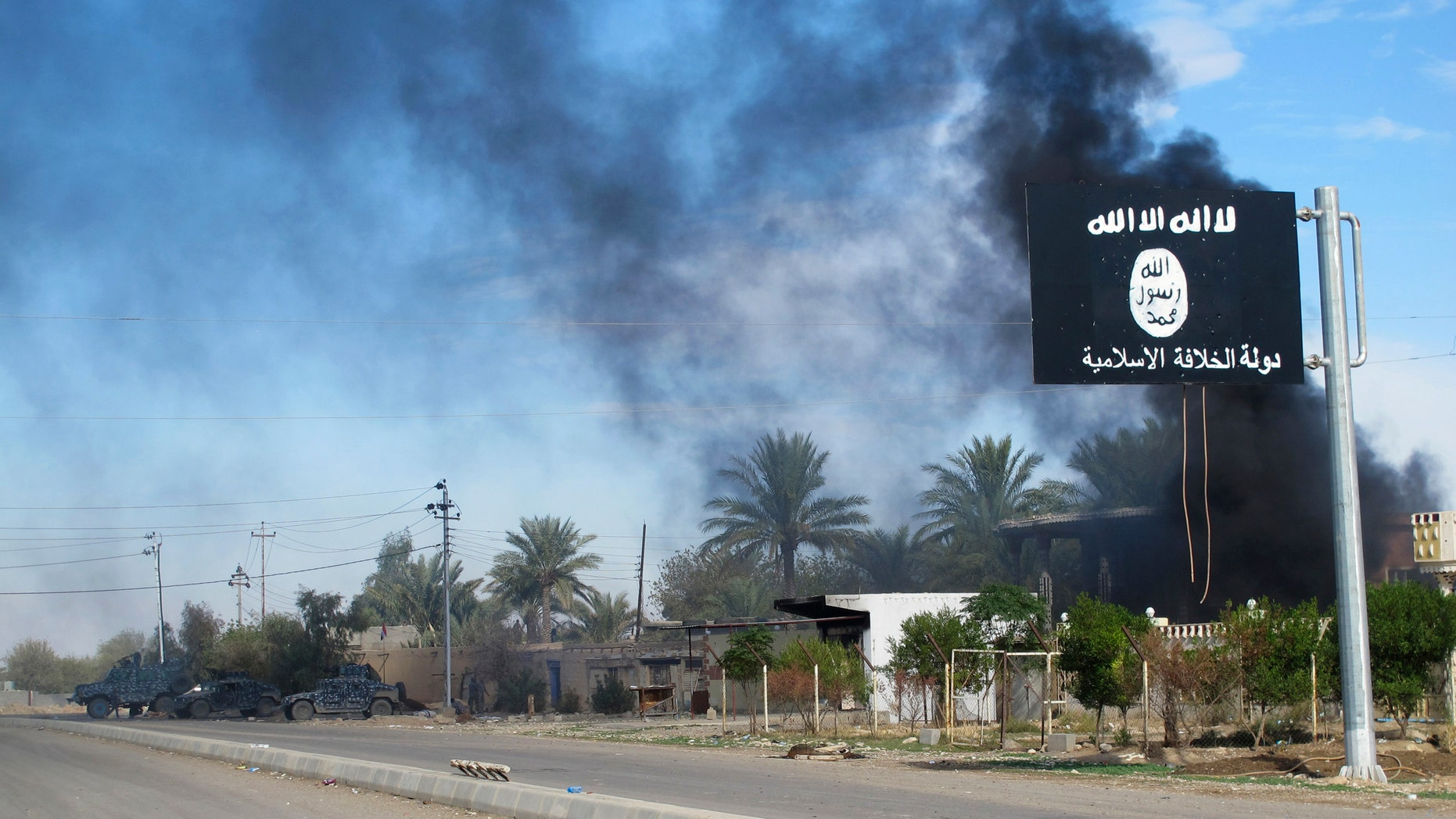 File photo - Smoke raises behind an Islamic State flag after Iraqi security forces and Shiite fighters took control of Saadiya in Diyala province from Islamist State militants, Nov. 24, 2014. (REUTERS/Stringer)