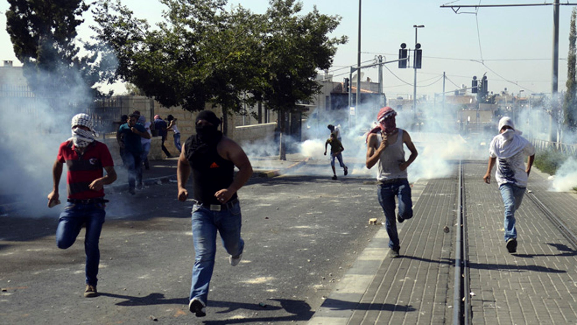July 4, 2014: Palestinians run away from tear gas as they clash with Israeli security forces during the funeral of 16-year-old Mohammed Abu Khdeir in Jerusalem.