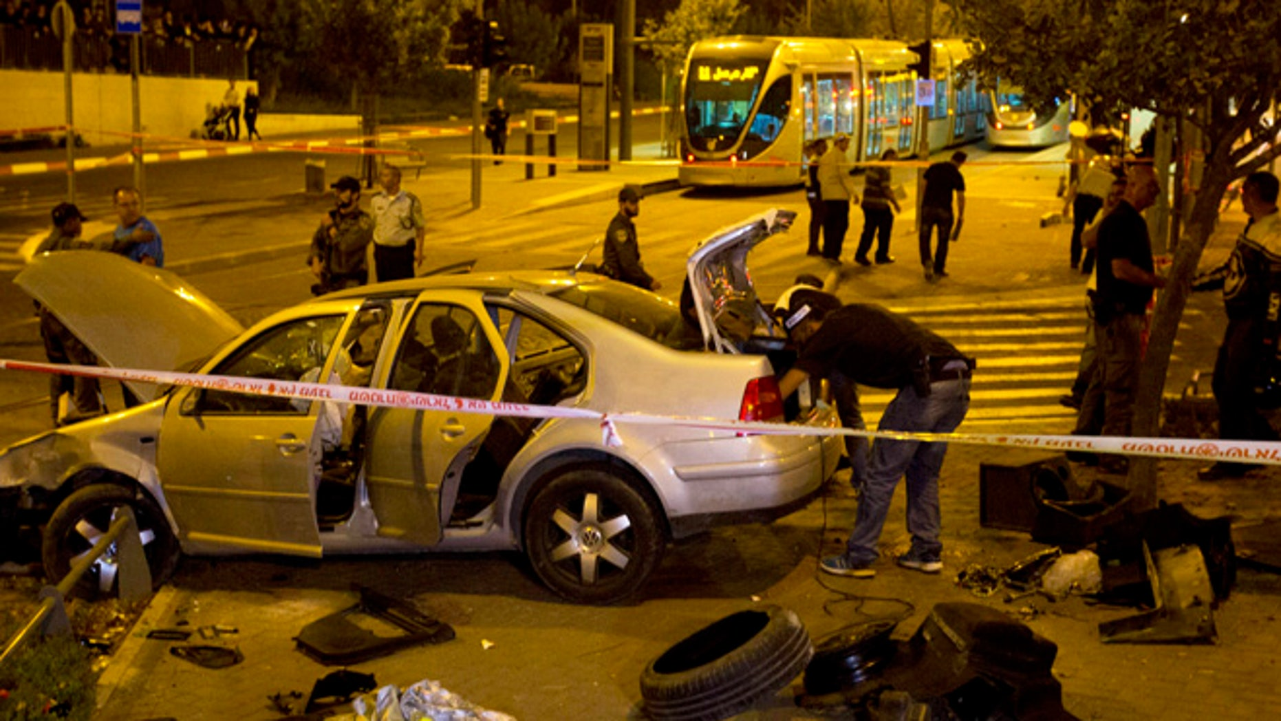 Oct. 22, 2014: Israeli police officers inspect a car at the scene of an attack in Jerusalem. A Palestinian motorist with a history of anti-Israel violence slammed his car into a crowded train station in Jerusalem on Wednesday, killing a three-month-old baby girl and wounding several people in what police called a terror attack.