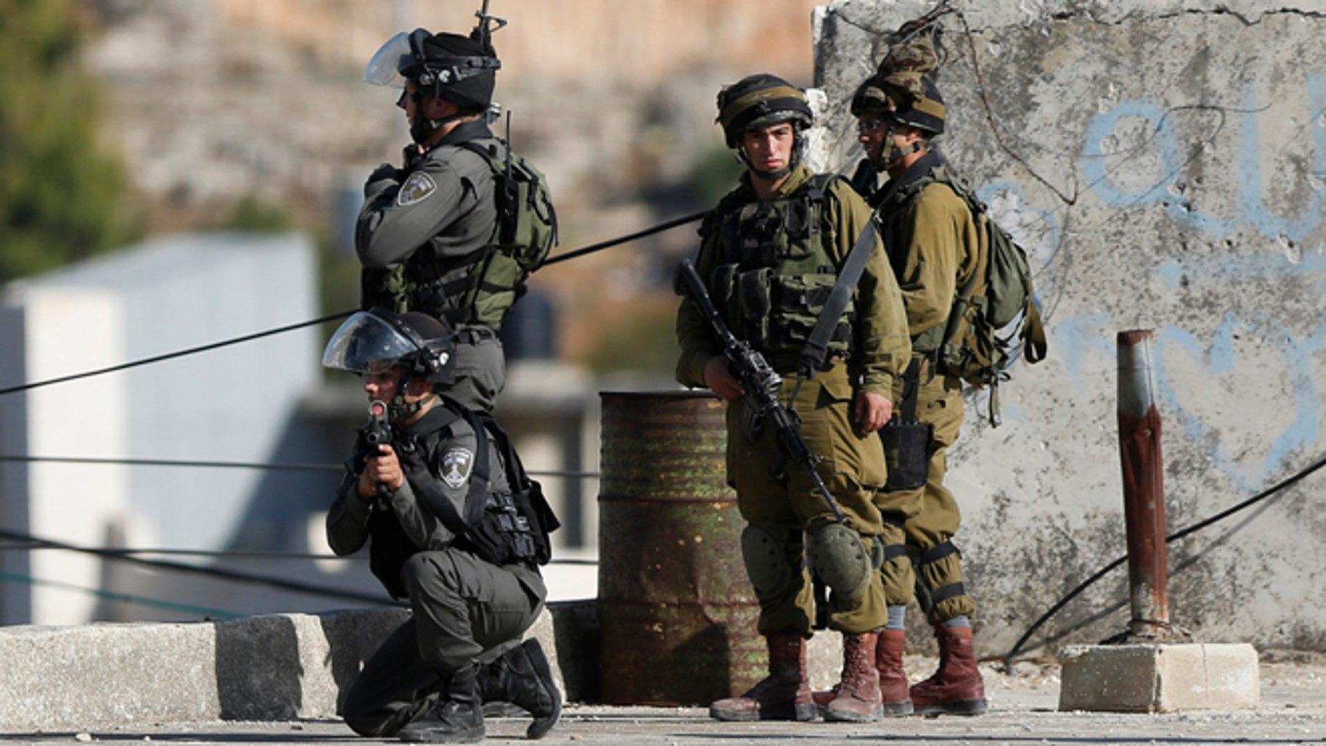 Nov 1, 2015: Israeli security troops take positions at the scene of a stabbing attempt, in the Beit Einun junction east of the West Bank city of Hebron. The Israeli military said soldiers shot a Palestinian who had tried to stab them on Sunday in the West Bank city of Hebron, in the latest violence of a bloody six-week spell. The military said the shooting took place during a violent riot and that no Israelis were harmed.