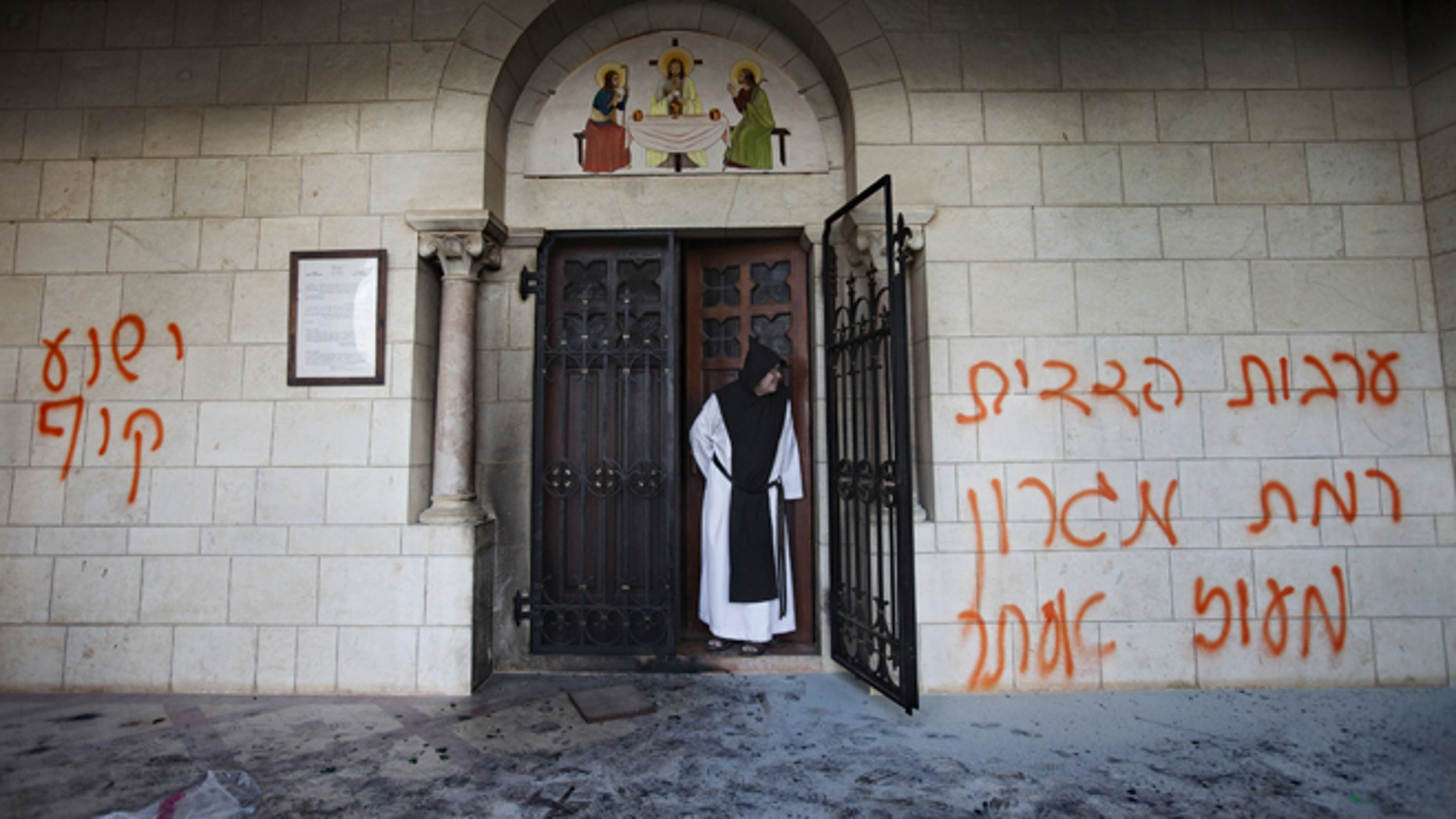 Sept. 4, 2012: A Catholic monk stands in a doorway of the Latrun Trappist Monastery where Israeli police say vandals spray-painted anti-Christian and pro-settler graffiti and set the monastery's door on fire, in Latrun, between Jerusalem and Tel Aviv, Israel.