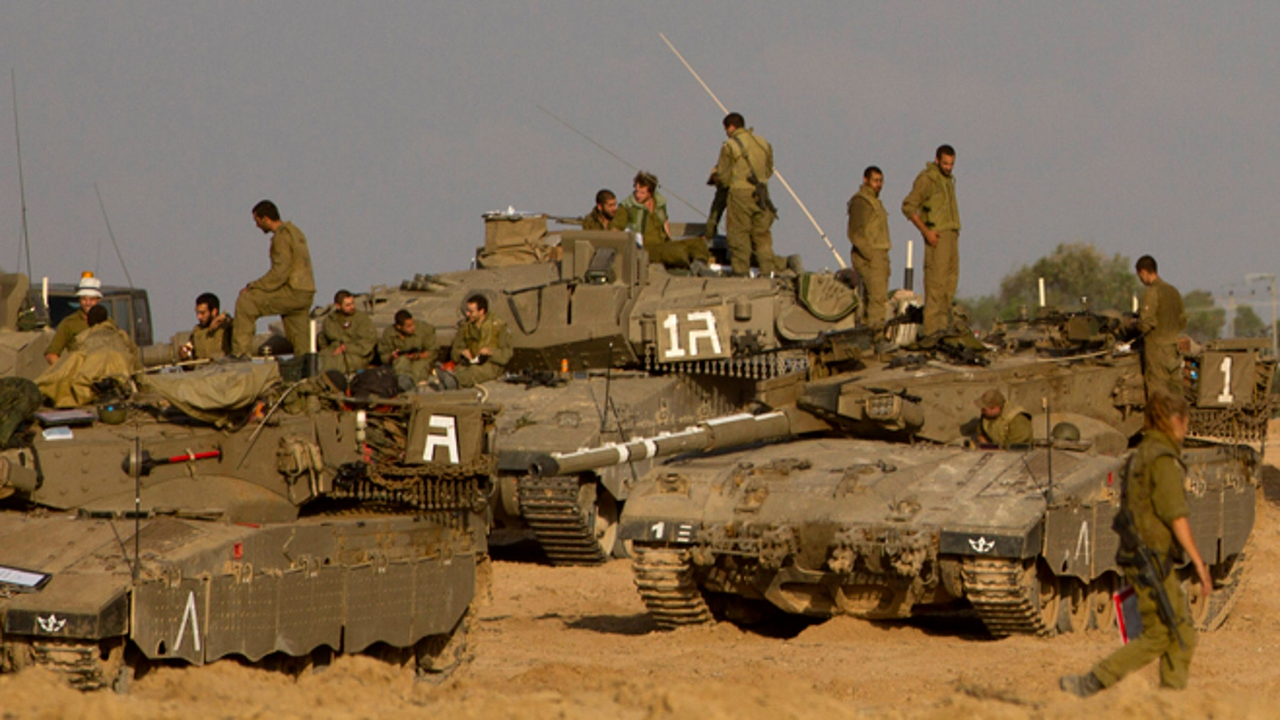Nov. 18, 2012: Israeli soldiers gather with their tanks and bulldozers in a gathering area near the Israel Gaza Strip border, in southern Israel. President Barack Obama on Sunday defended Israel's airstrikes on the Gaza Strip, but he warned that escalating the offensive with Israeli ground troops could deepen the death toll and undermine any hope of a peace process with the Palestinians.