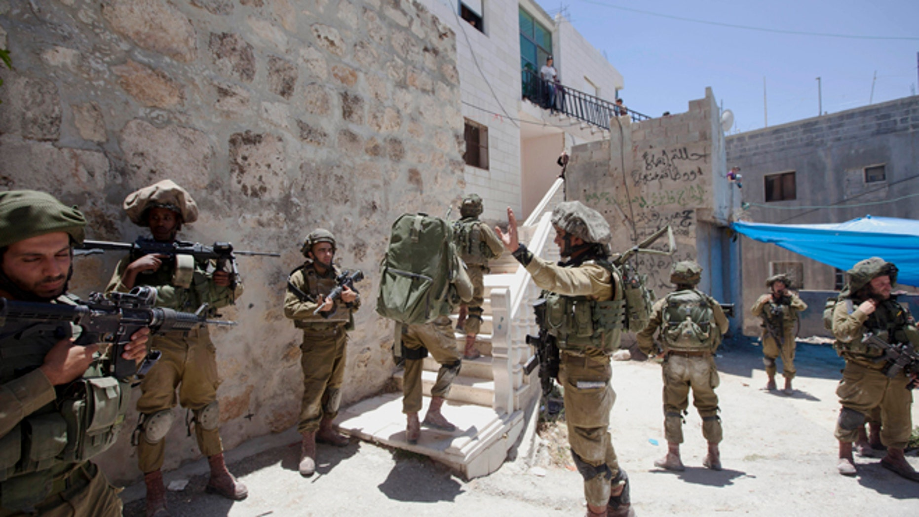 June 15, 2014: Israeli soldiers patrol during a military operation to search for three missing teenagers outside the West Bank city of Hebron. Israeli troops on Sunday arrested some 80 Palestinians, including dozens of members of Hamas, in an overnight raid in the West Bank as Prime Minister Benjamin Netanyahu accused the Islamic militant group of kidnapping three teenagers who went missing nearly three days ago. (AP/Majdi Mohammed)