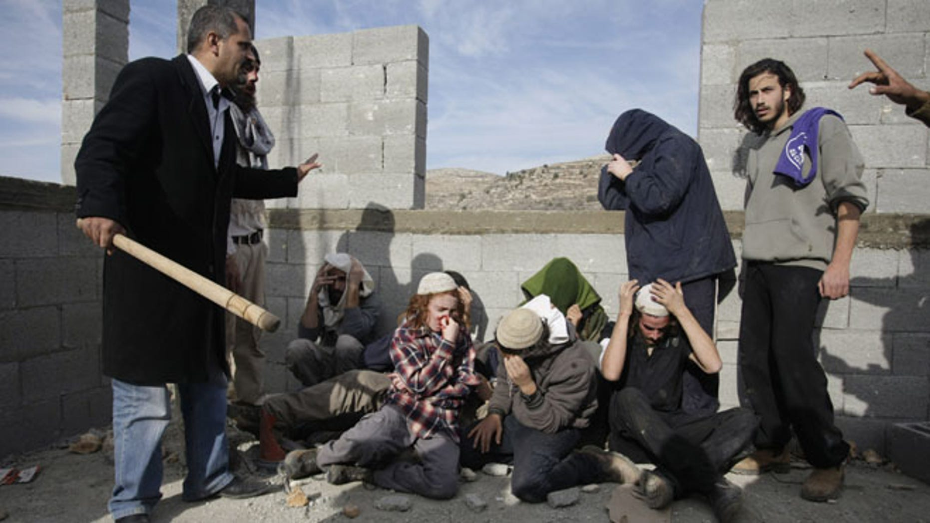Tuesday, Jan. 7, 2014, Injured Israeli settlers are detained by Palestinian villagers in a building under construction near the West Bank village of Qusra, southeast of Nablus.