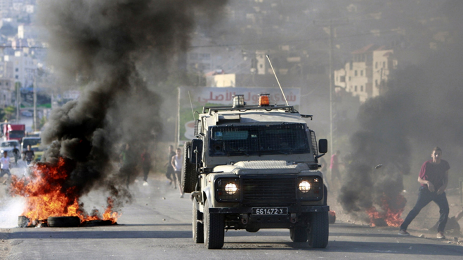 June 17, 2014: An Israeli army vehicle drives past burning tires during a search operation in the West Bank refugee camp of Jenin. (AP)