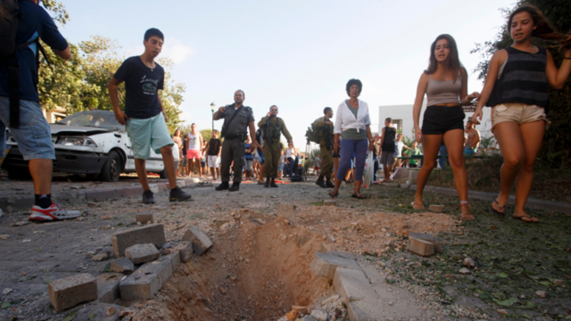 Aug. 22, 2013: Israelis look at the crater caused by the impact of a rocket fired from Lebanon in kibbutz Gehser HaZiv outside Nahariya in northern Israel.