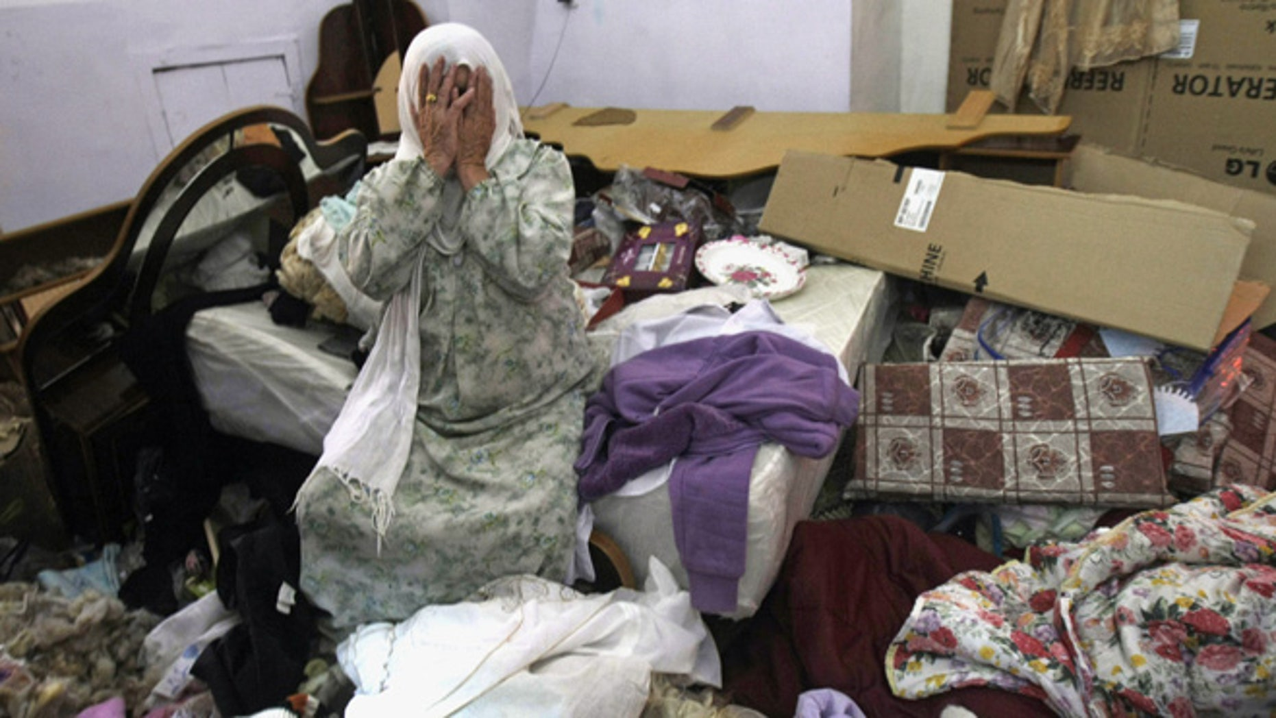 June 22, 2014: A Palestinian woman cries in her home after a raid by Israeli troops as the army continues feverish searches for three missing Israeli teens, in Salim village near the West Bank city of Nablus. (AP)