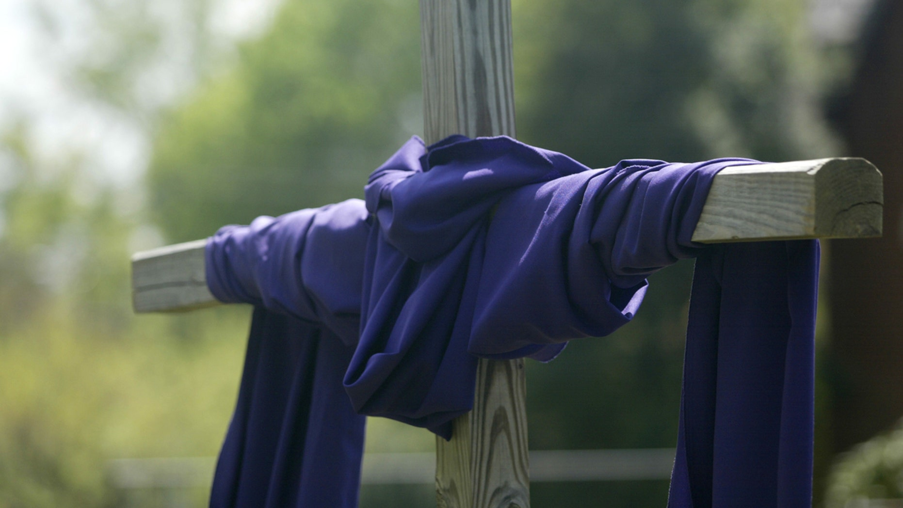 """A wooden cross is wrapped with purple cloth, symbolizing the season of Lent and Easter."""