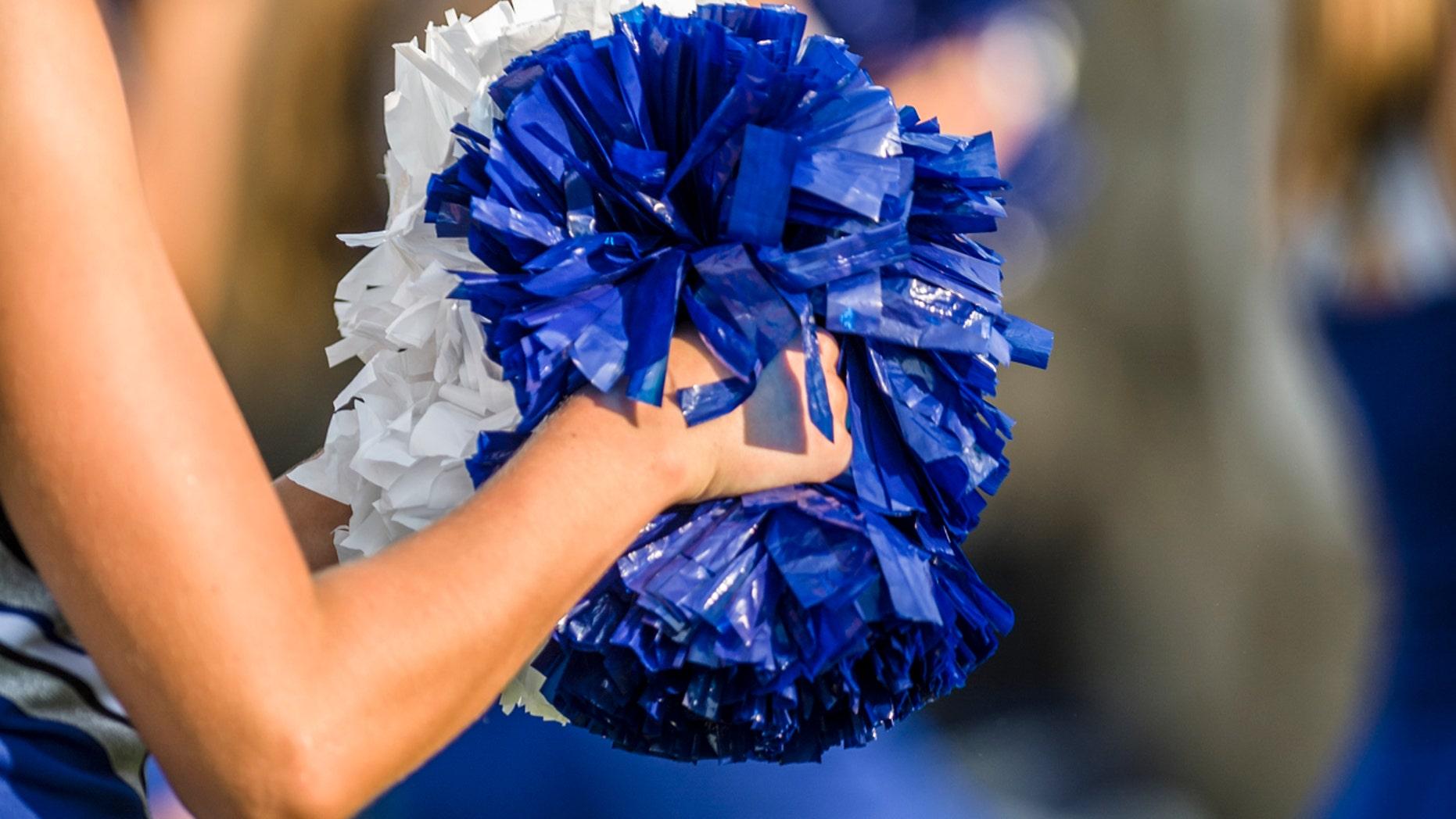 Cheerleader shaking blue and white pom poms