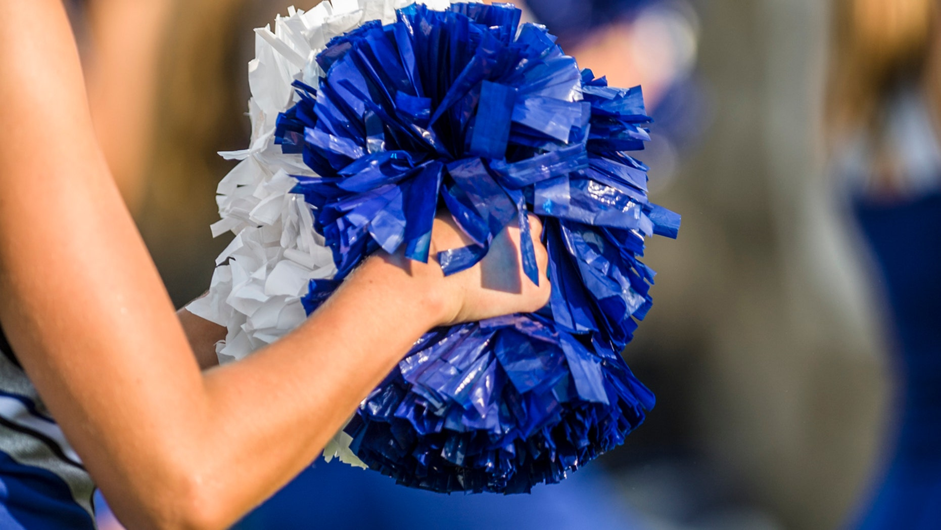 Cheerleader shaking blue and white pom poms