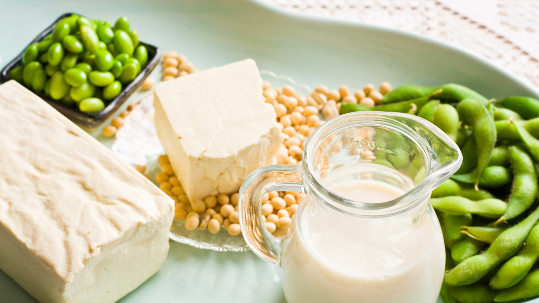 A variety of soy milk and soybean products. They are sitting in a soft aqua colored tray. There is a brick of firm tofu and a small pitcher of soy milk. On the right are some green soy beans and in back there is a small dish of shelled soybeans.