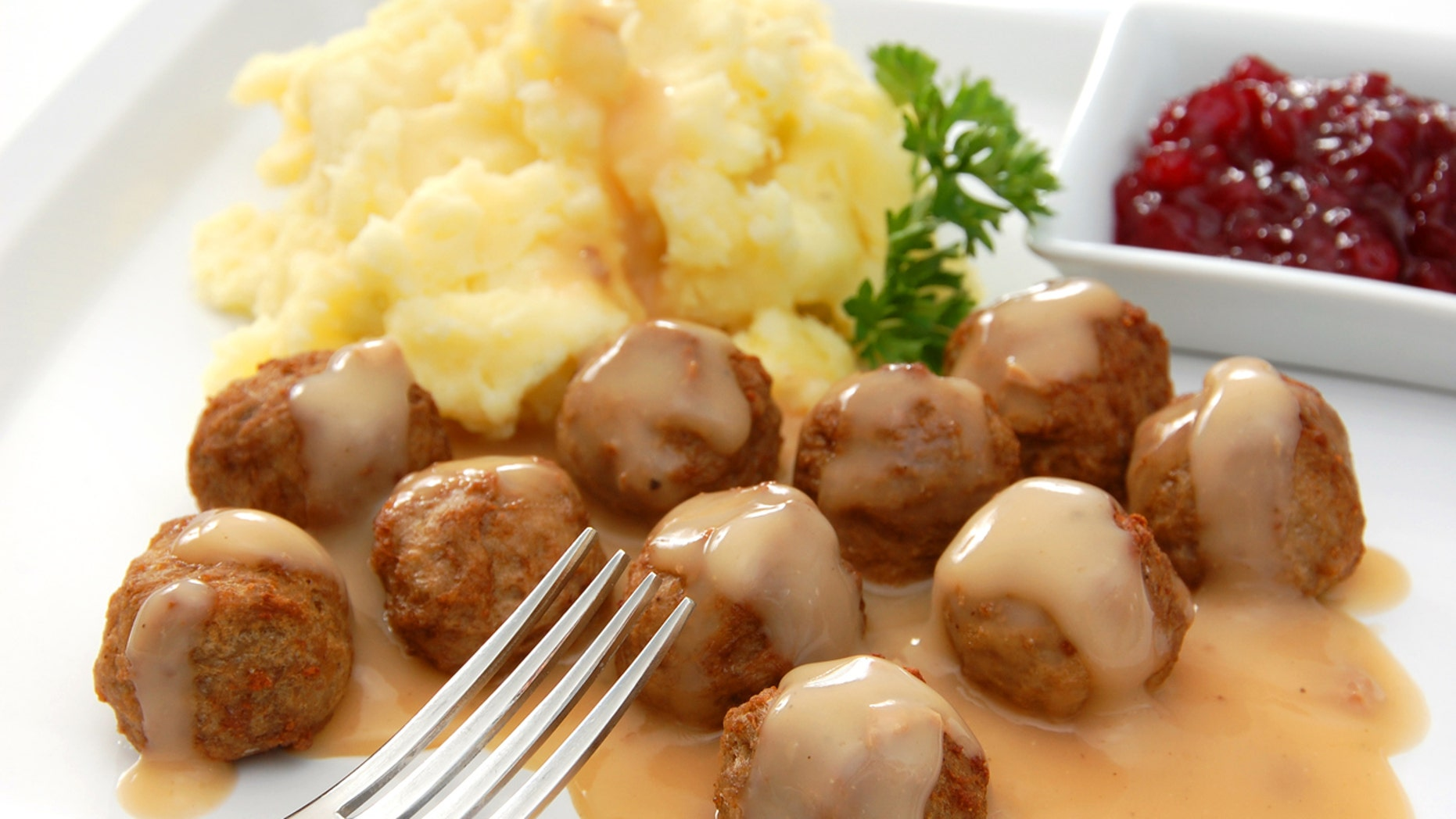 """Swedish meatballs served with the traditional accompaniments of gravy, mashed potatoes, and lingonberry sauce.More images from this series:"""