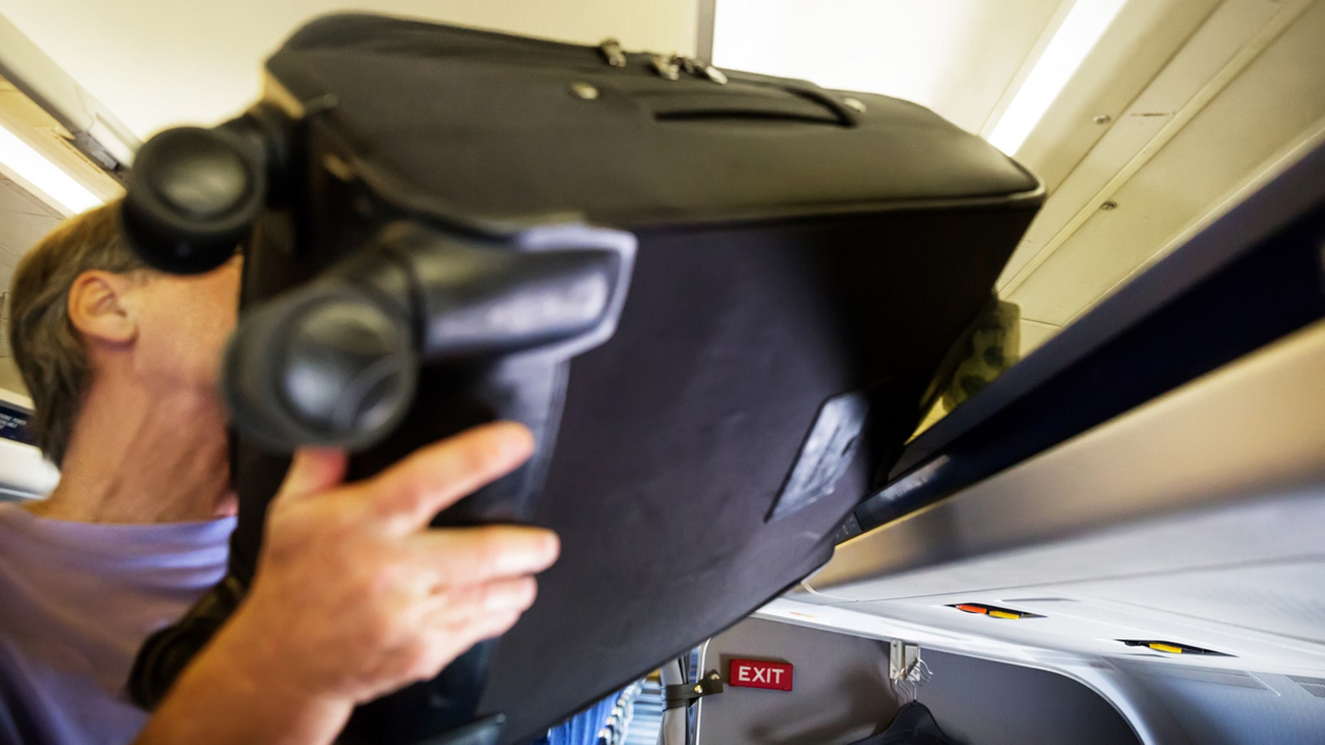 In the viral video, an unidentified passenger is seen struggling to push his suitcase into the overhead bin.