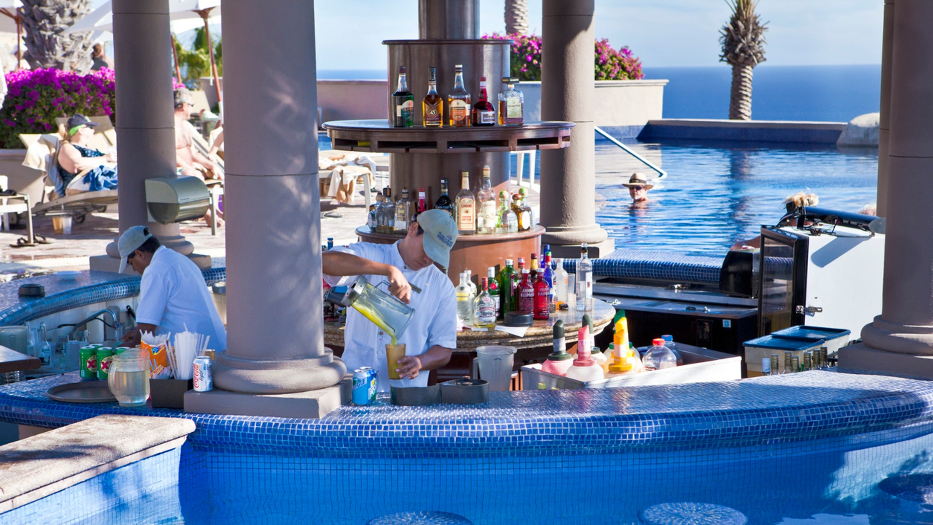 Bartenders work around a pool bar in Cabo San Lucas.