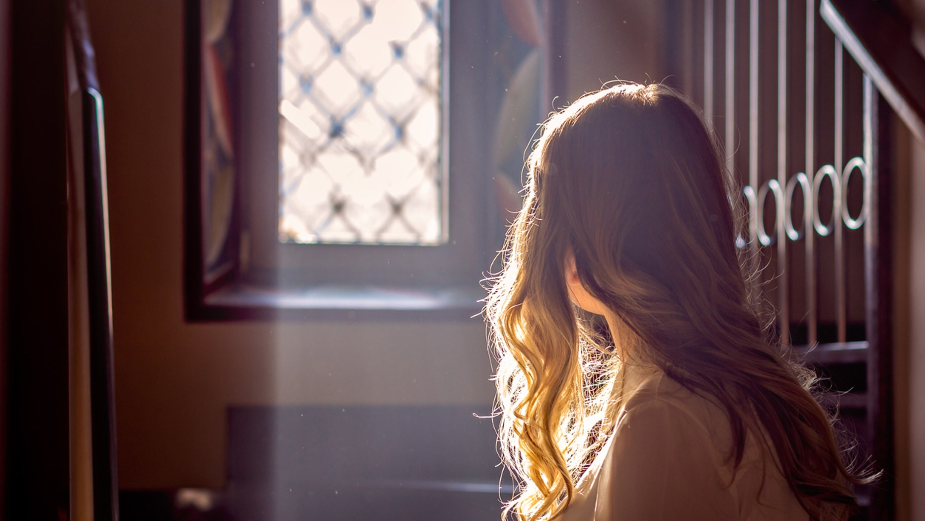 child looking out the window of the church while the light falls on her