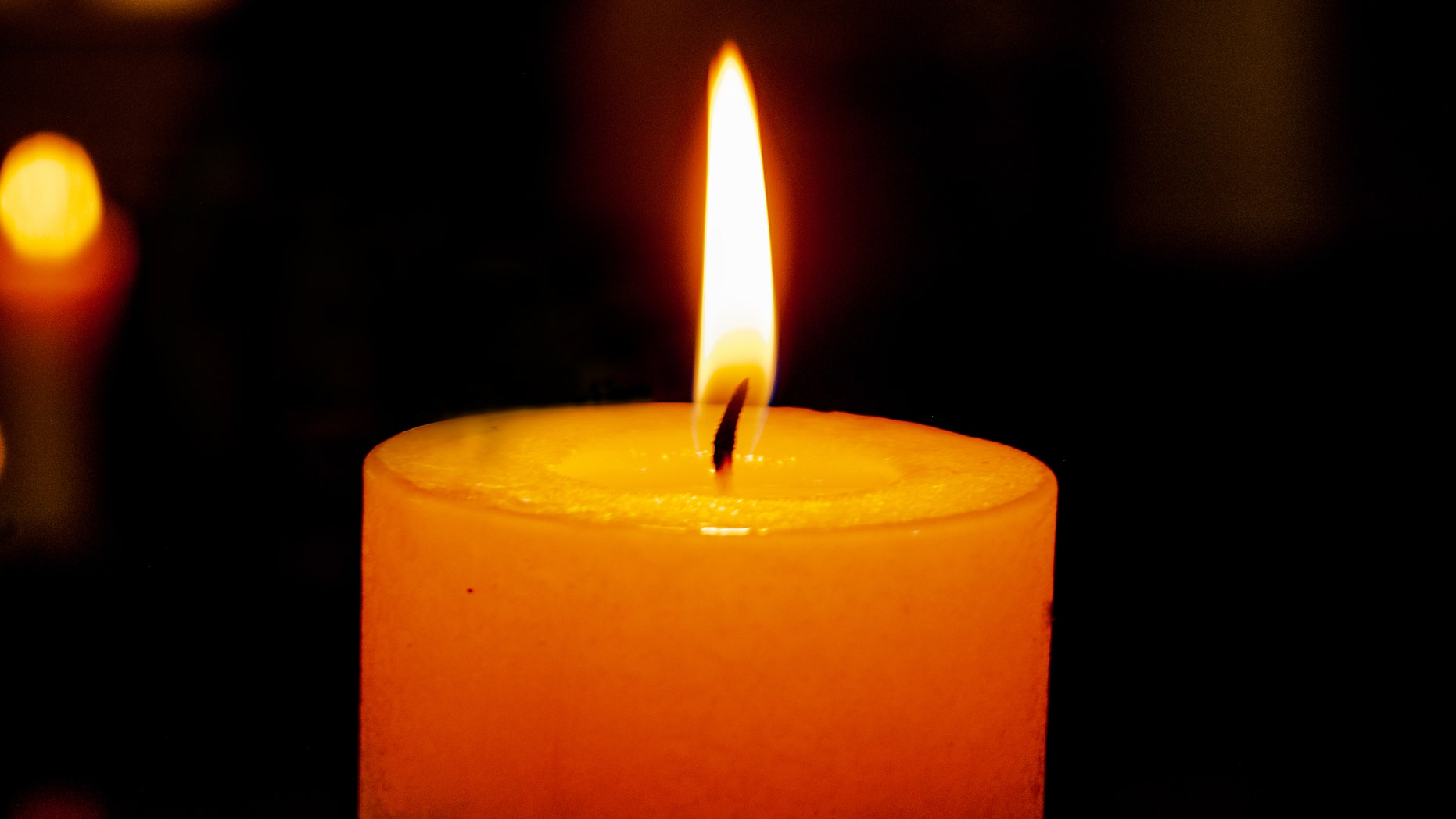 single burning candle on a dark background with reflection