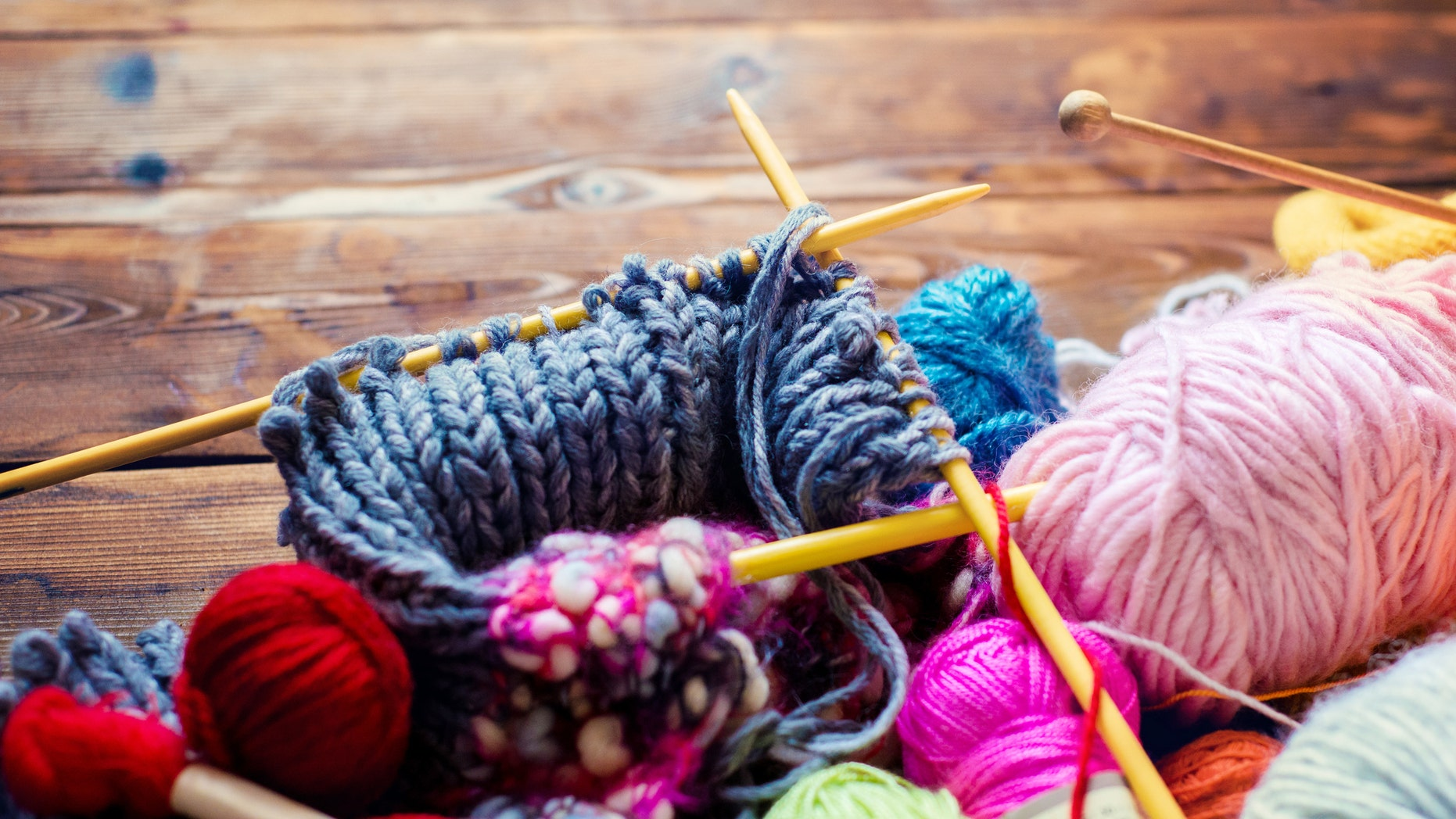 view from above on a wooden table with lots of balls of wool, knitting needles and other tools.  Place for text and the word craft