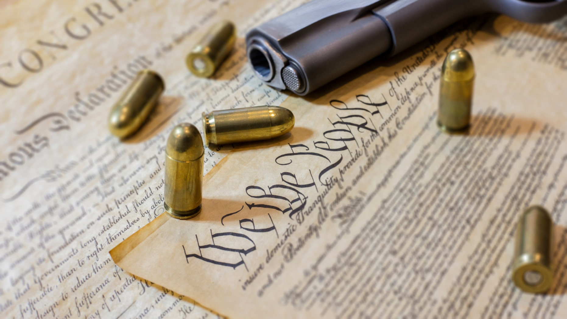 A stock photograph the of the US Constitution and a gun with bullets. Perhaps communicating USA Gun control. Photographed at 50mp with the Canon EOS 5DSR.