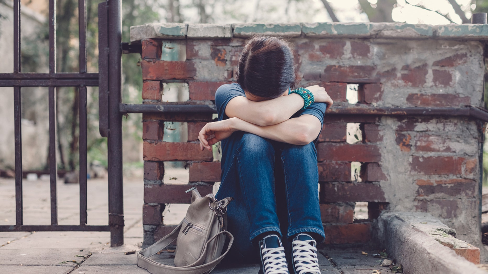 Crying girl with head in hands sitting on the ground