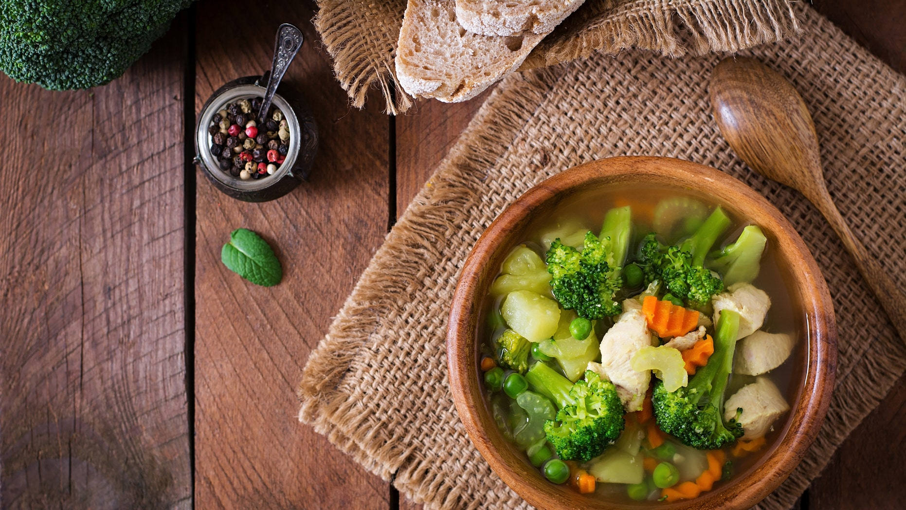 Chicken soup with broccoli, green peas, carrots and celery in  bowl on a wooden background in rustic style. Top view