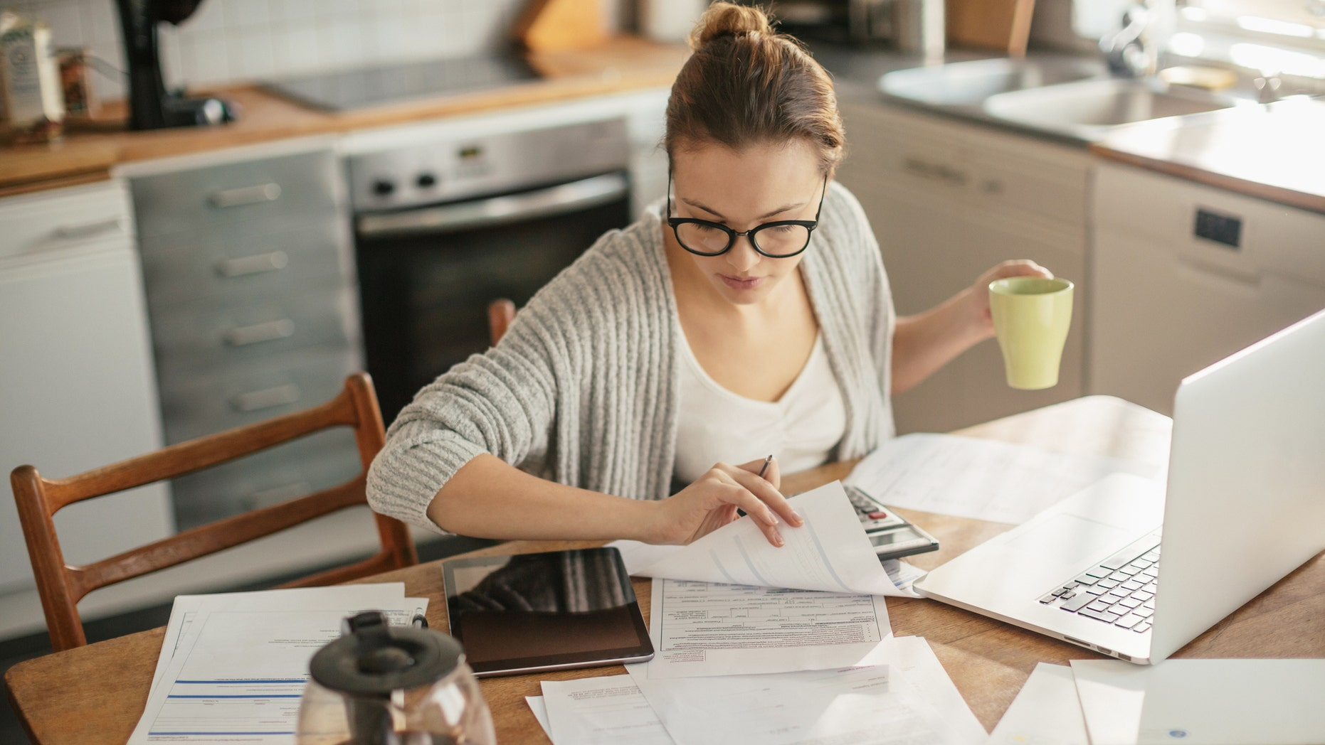 Close up of a young woman sitting in kitchen and  going through her financials