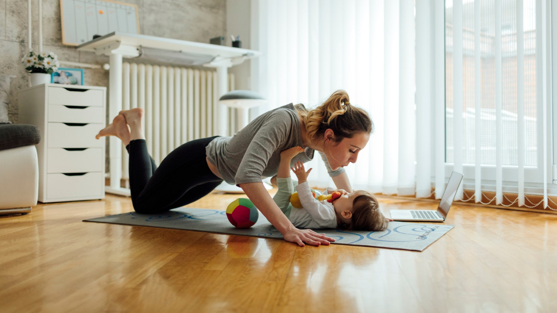 Shot of an attractive young woman with her baby girl while doing exercise. Woman working pushups and baby lying on exercise mat. They exercise in a living room. Woman watching exercise on laptop.