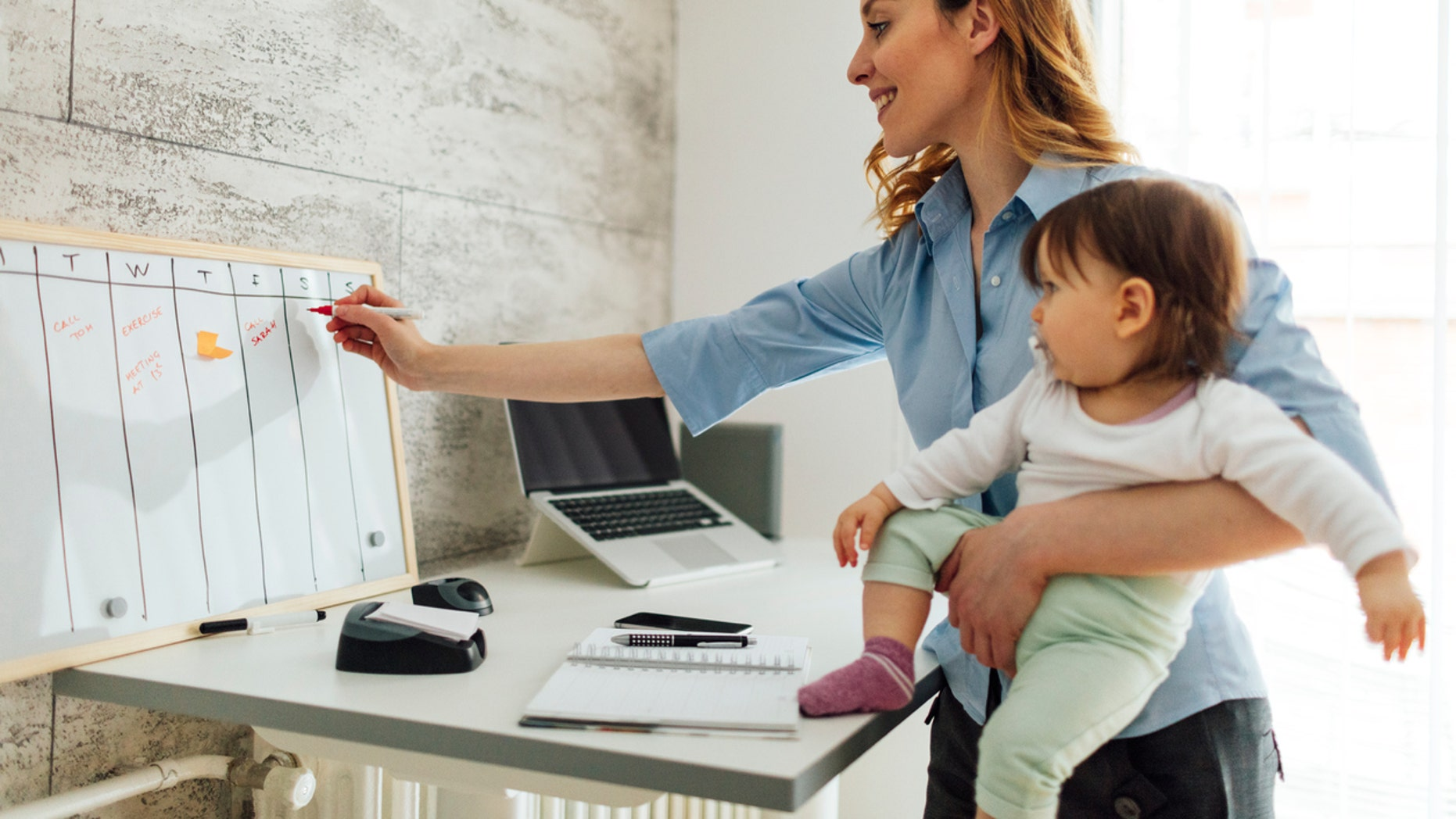 Mother working from home while carrying her cute baby girl. She is writing on whiteboard, entering into the schedule. She is happy and cheerful.