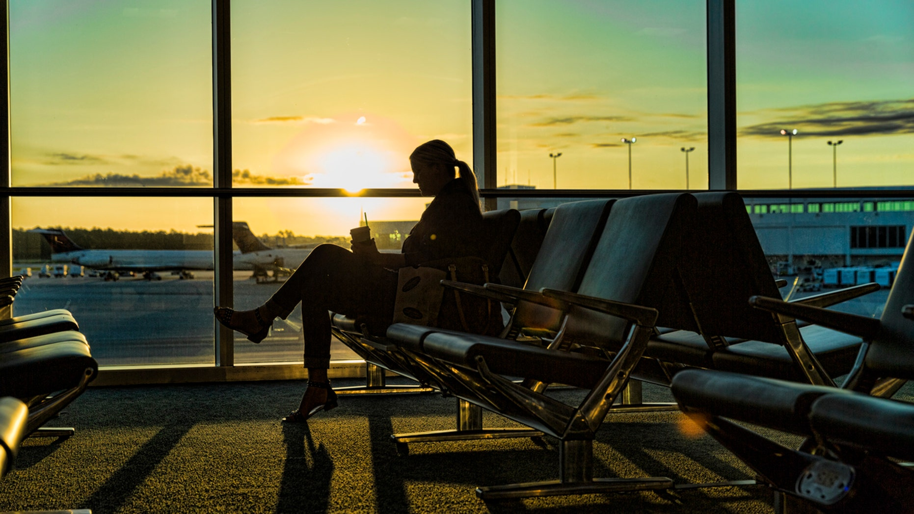 A woman sits at the airport waiting for her plane. She is enjoying a drink and snack as the sun rises.