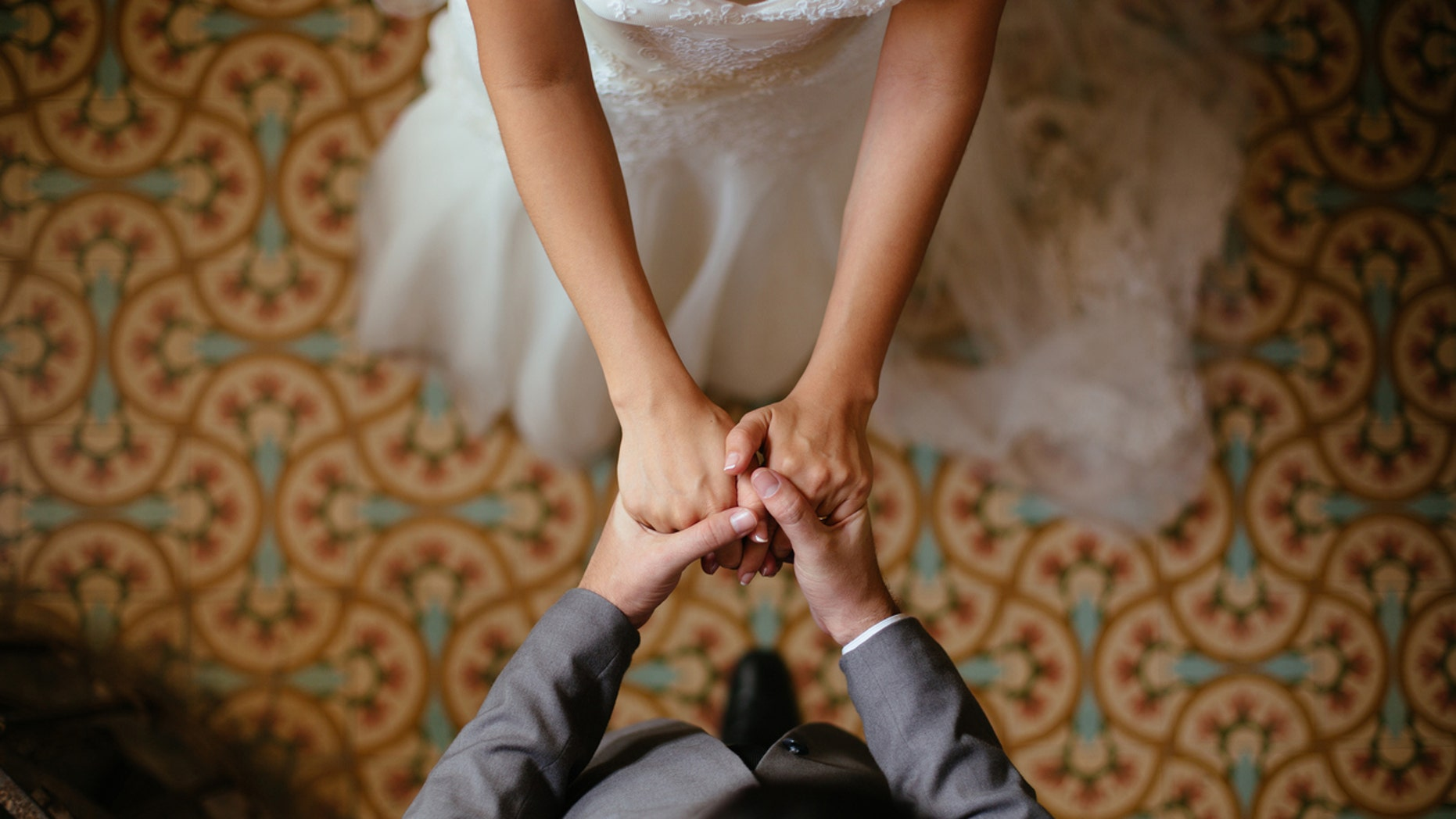 A close up shot of a bride and groom holding hands from a top view.