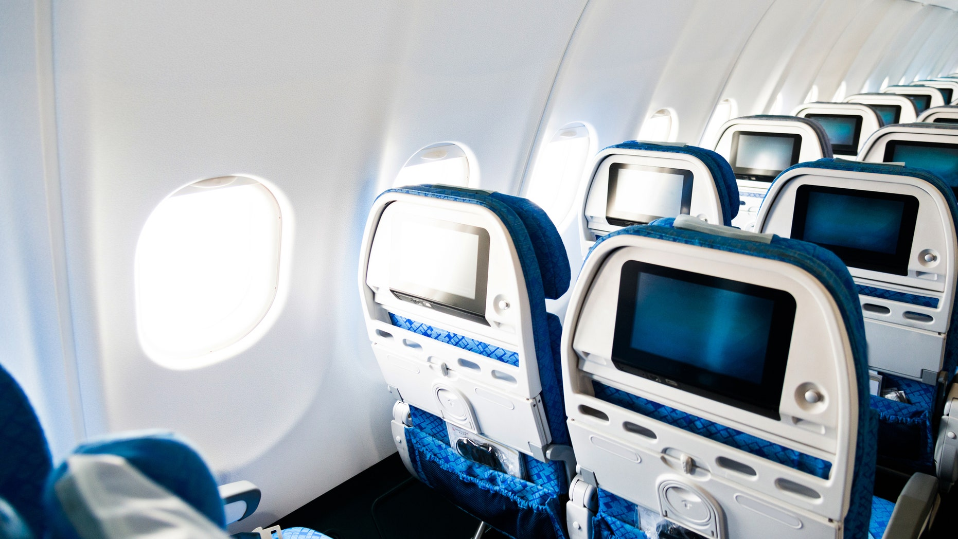 Airplane seat with Tv screens in chairs back.