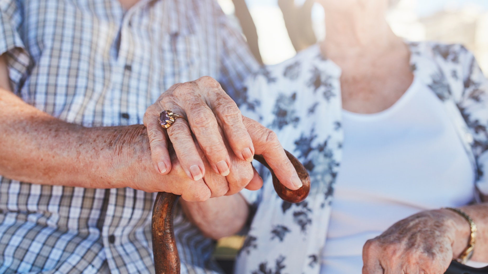 Cropped shot of senior couple holding hands while sitting together. Focus on hands on walking stick.