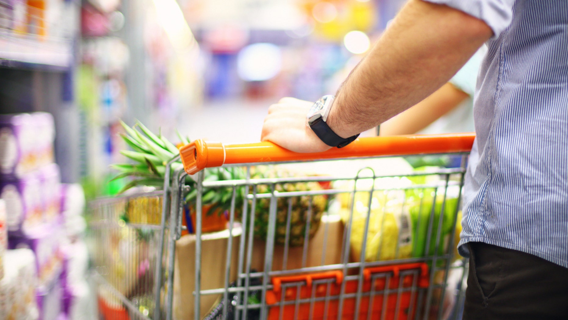 Rear view of unrecognizable mid-aged man in supermarket.He's pushing shopping car almost fully packed with groceries.Shelves with products stretch deep in background out of focus. He's wearing light blue striped shirt with rolled back sleeves,brown pants and a wristwatch.