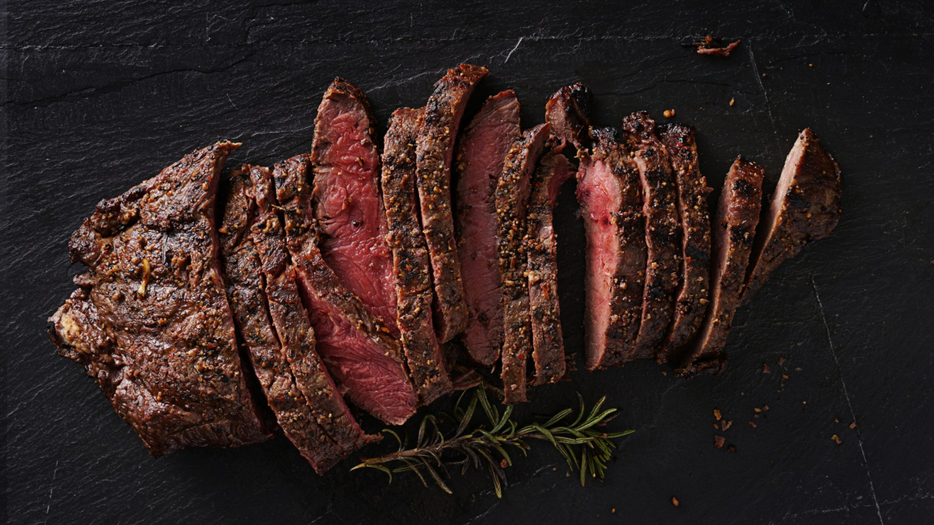 grilled flat iron steak shot in flat lay style from overhead on dark slate