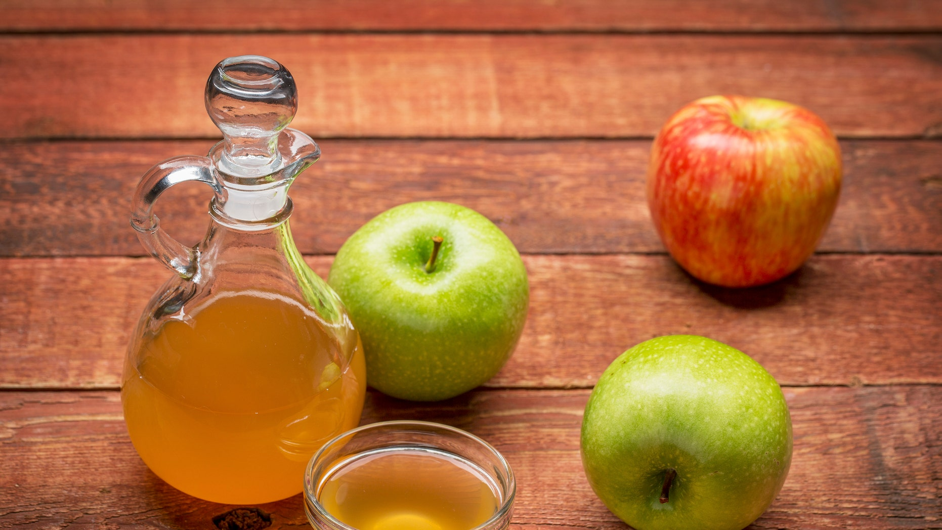 unfiltered, raw apple cider vinegar with mother - a cruet with a small glass  bowl surrounded by fresh  apples on rustic wood