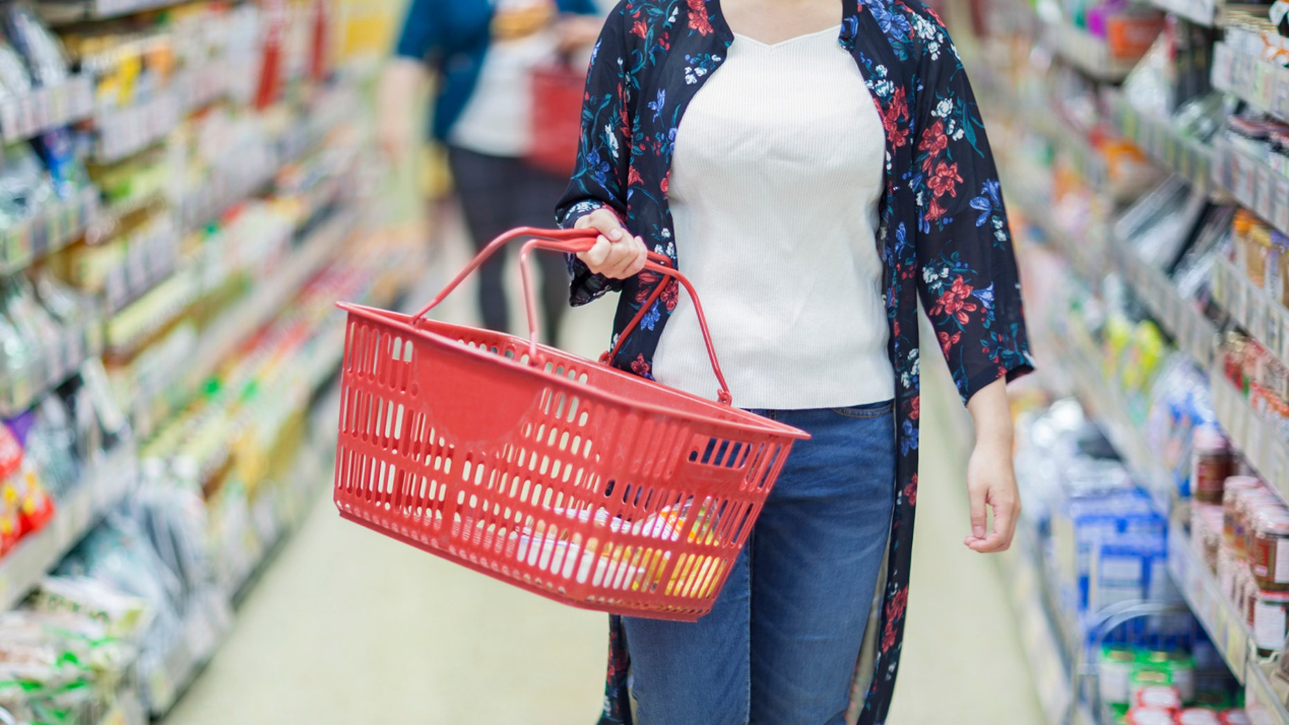 A young Japanese girl is shopping in a supermarket.