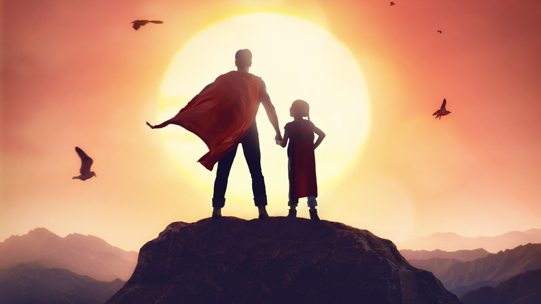 Happy loving family. Father and his daughter playing outdoors. Daddy and his child girl in an Superhero's costumes.