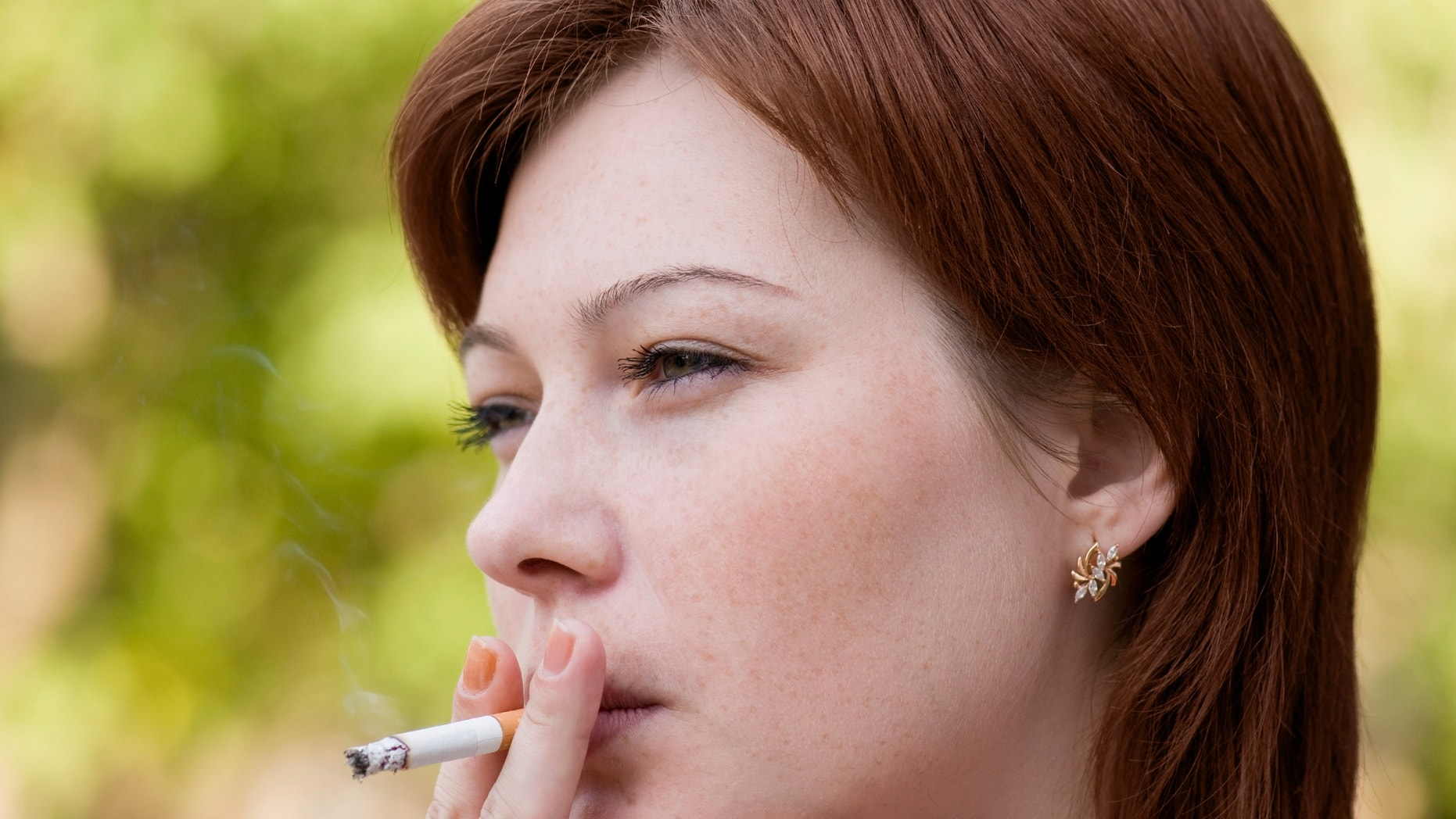 The young woman who is smoking a cigarette and carrying away a smoke in air