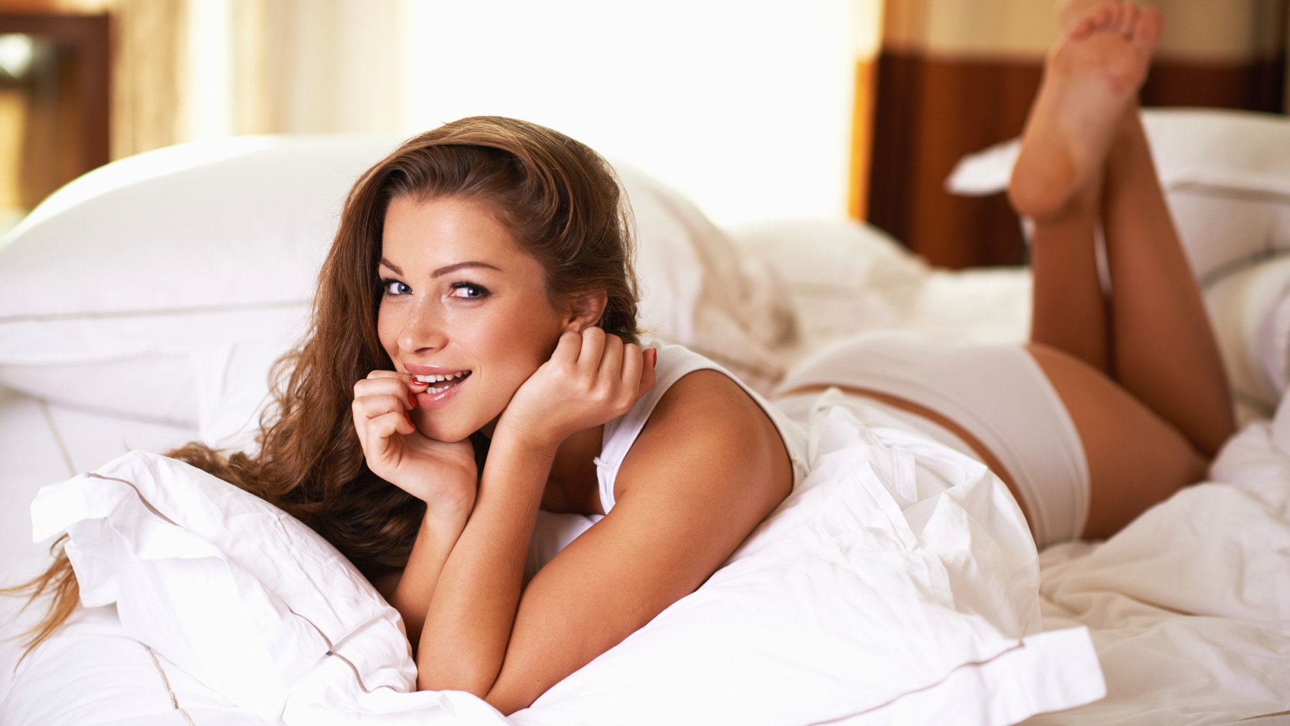Shot of a gorgeous young woman in pajamas lying on a bed