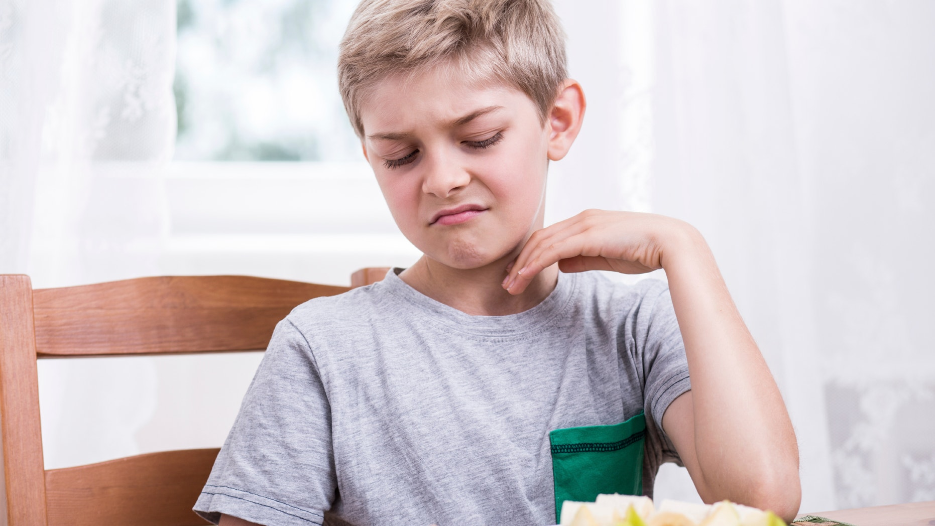Blonde boy refusing to eat healthy apple